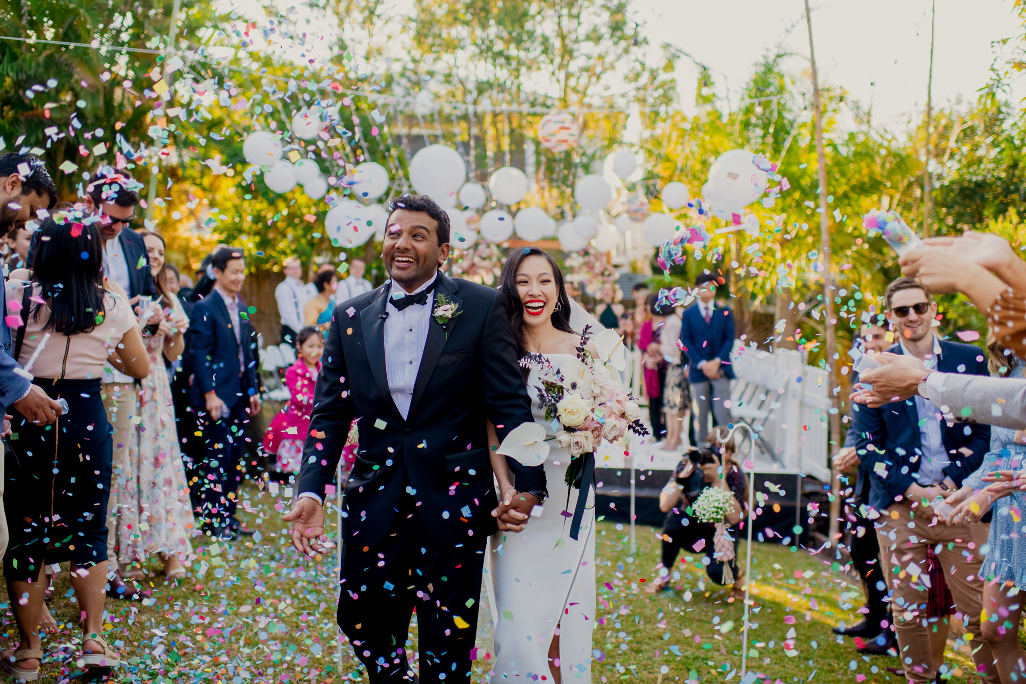 Bride and groom walk down the aisle and laugh as guests shower them in colourful confetti