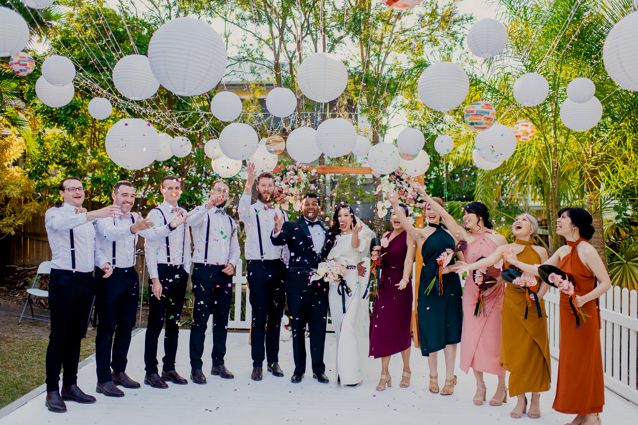 Bridal party smiles as they throw colourful confetti in the air
