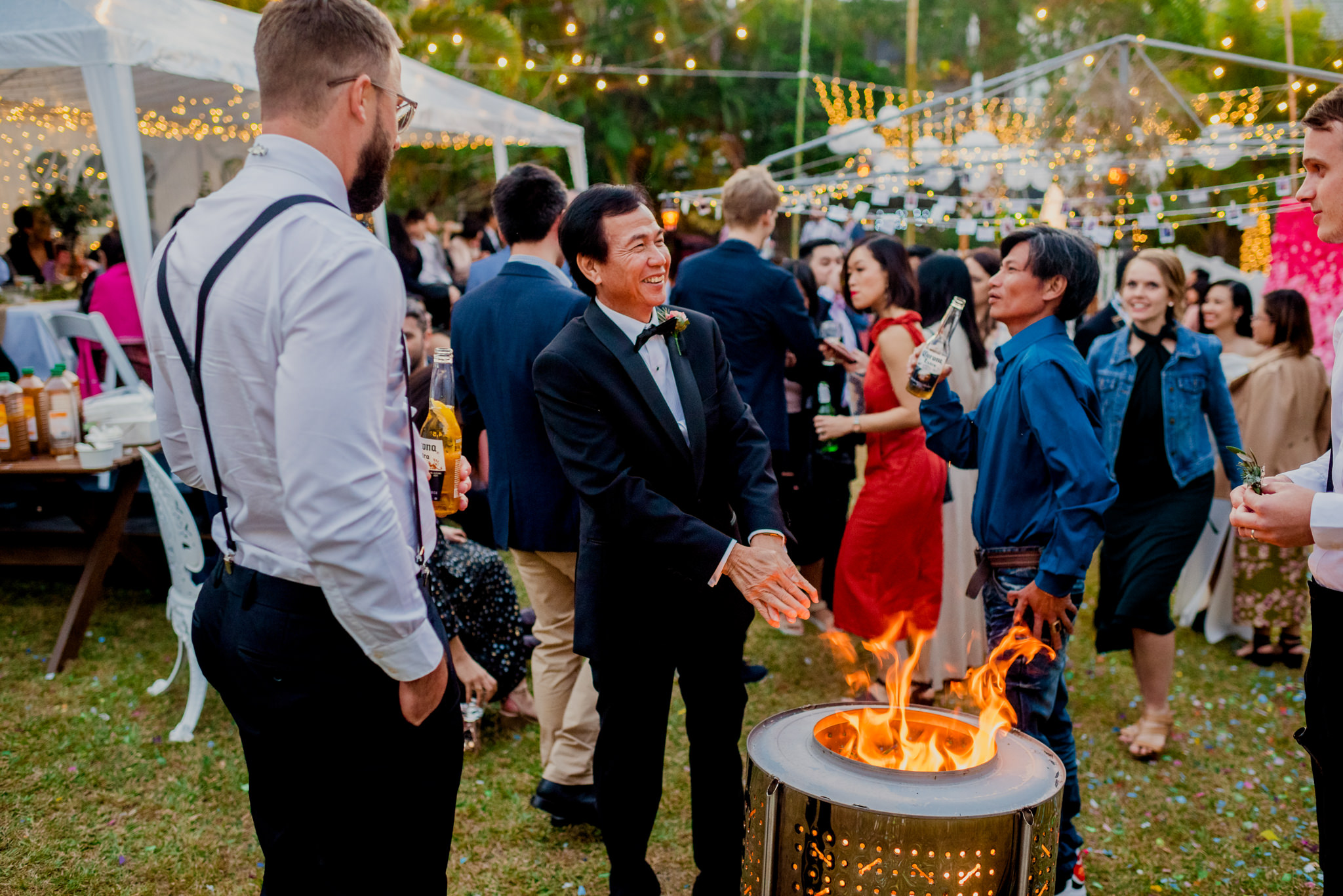 Father-of-the-bride warms his hands in front of a fire pit