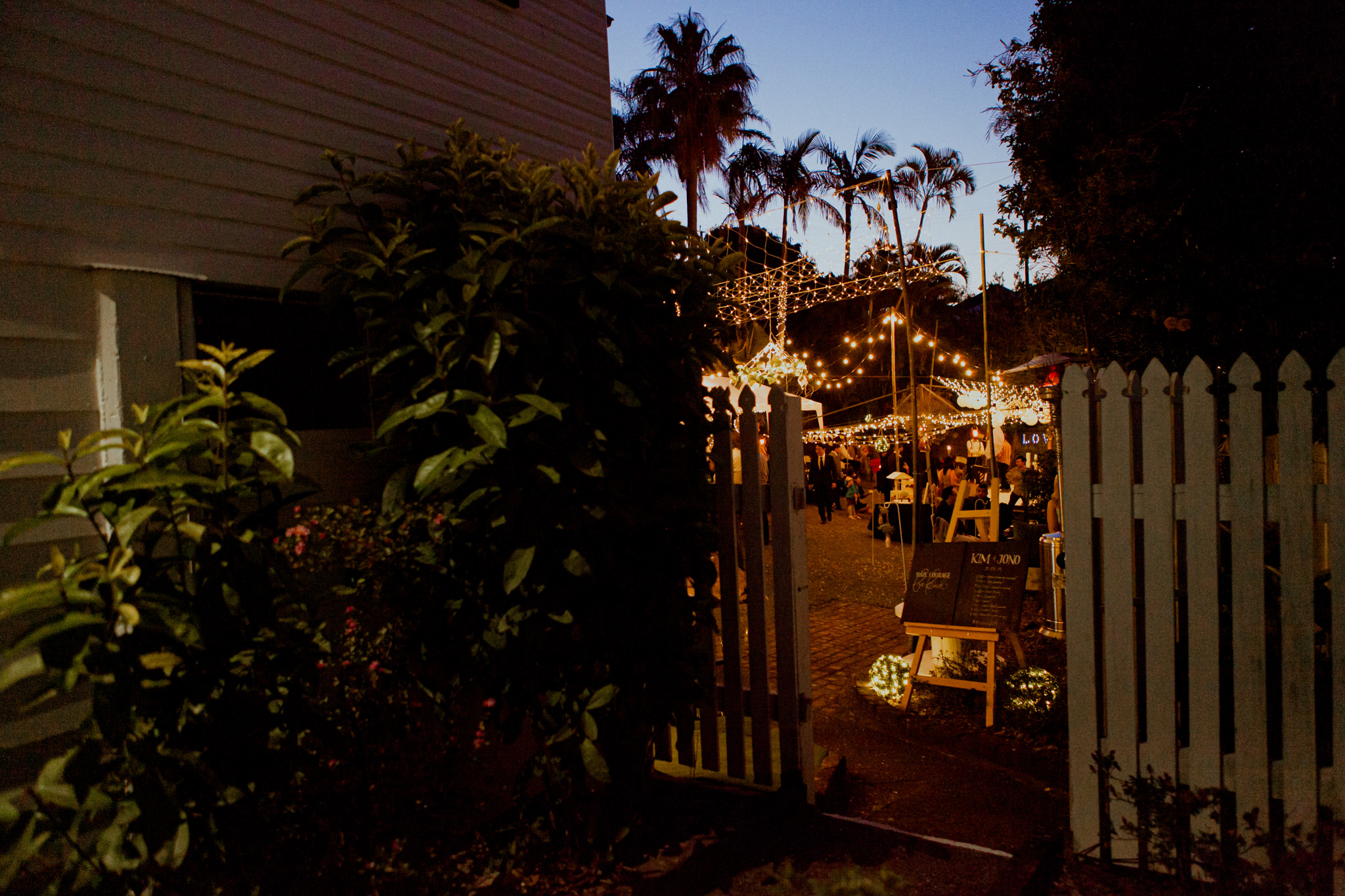 Side alley of a house leading to a backyard party lit with fairy lights