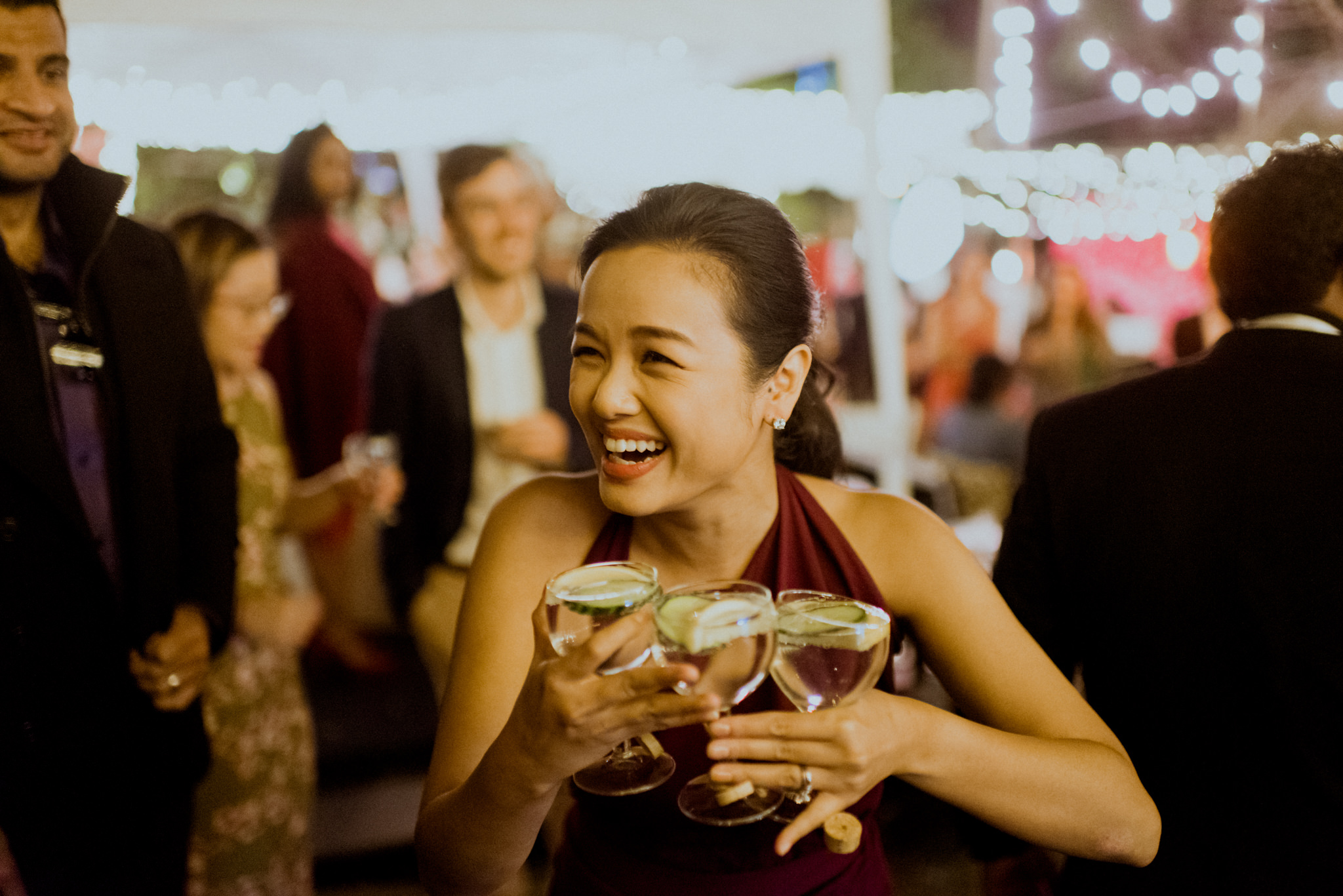 Asian woman laughs as she holds three glasses full of alcohol