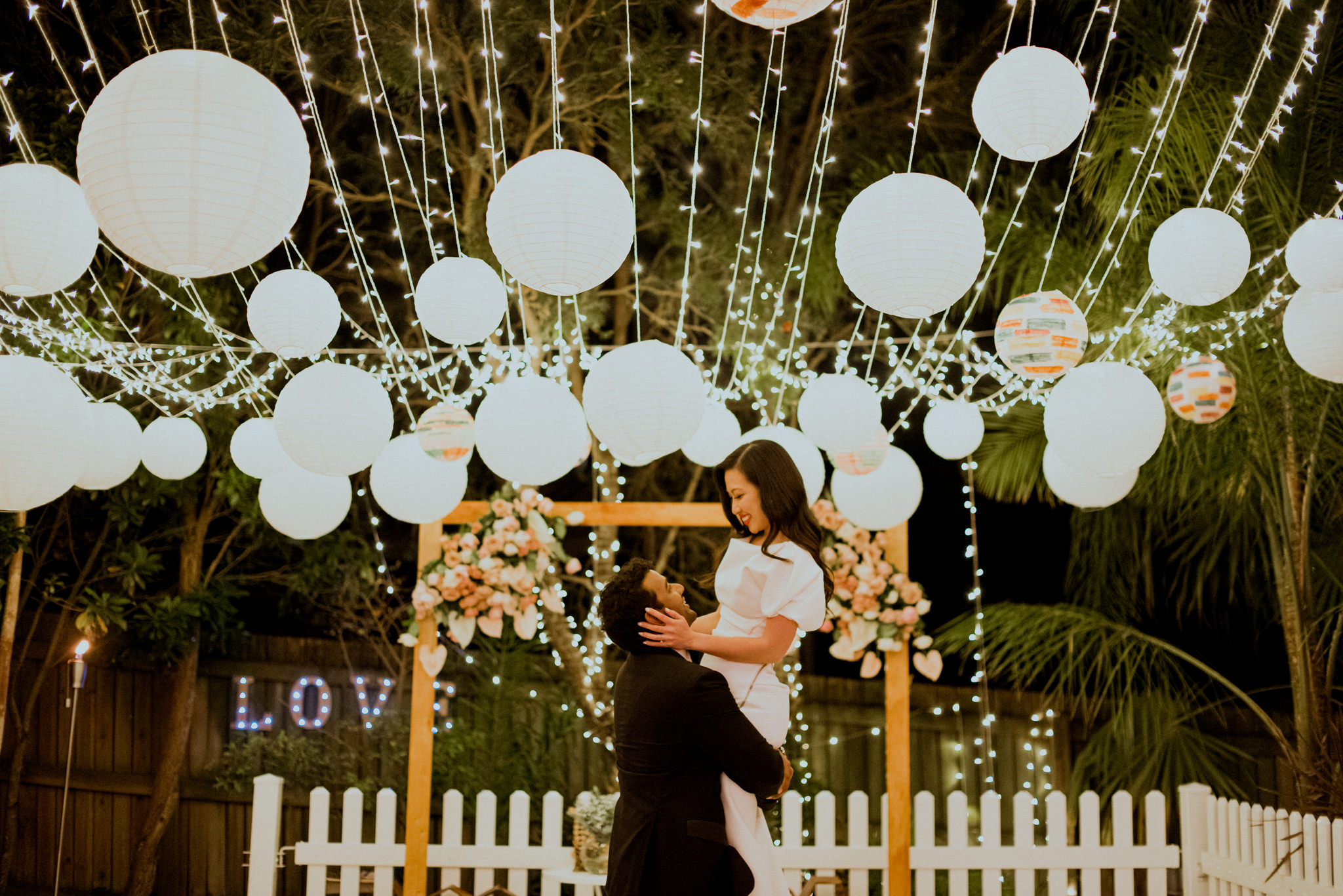 Bride and groom dancing together underneath circular lanterns and fairy lights