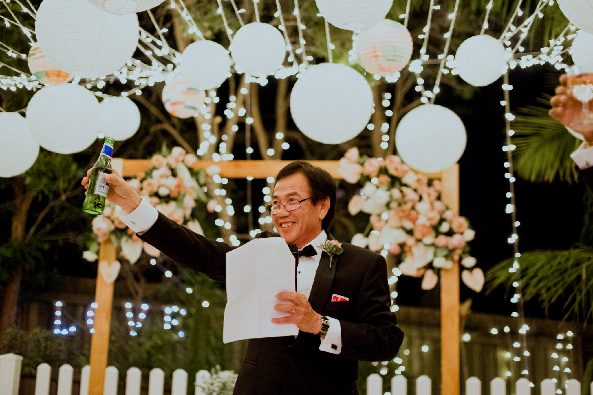 Man gives speech and toasts underneath circular lanterns and fairy lights