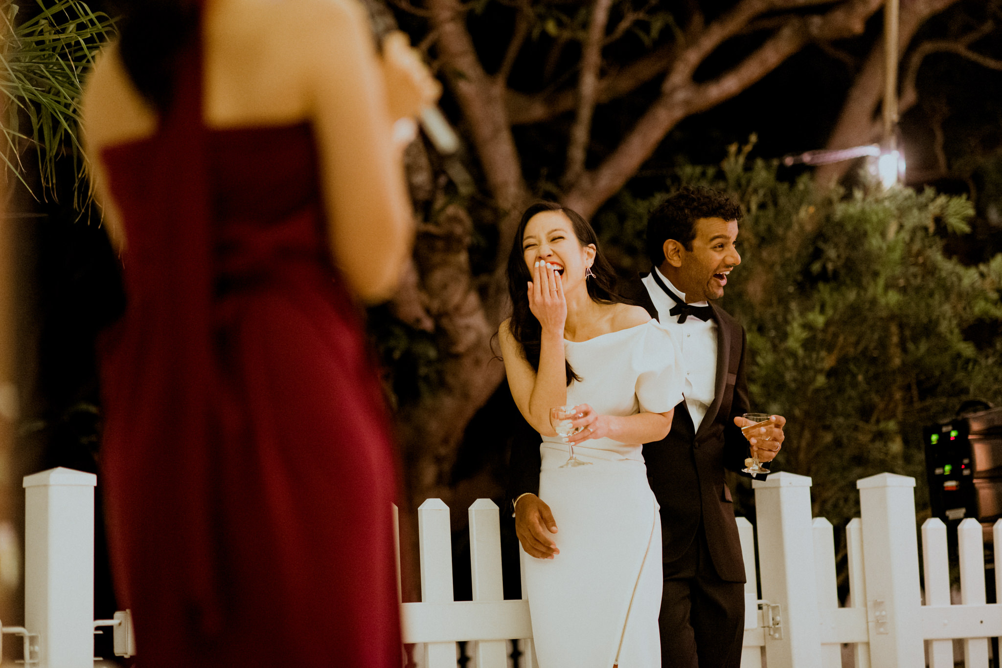 Bride and groom laughing as bridesmaids delivers speech