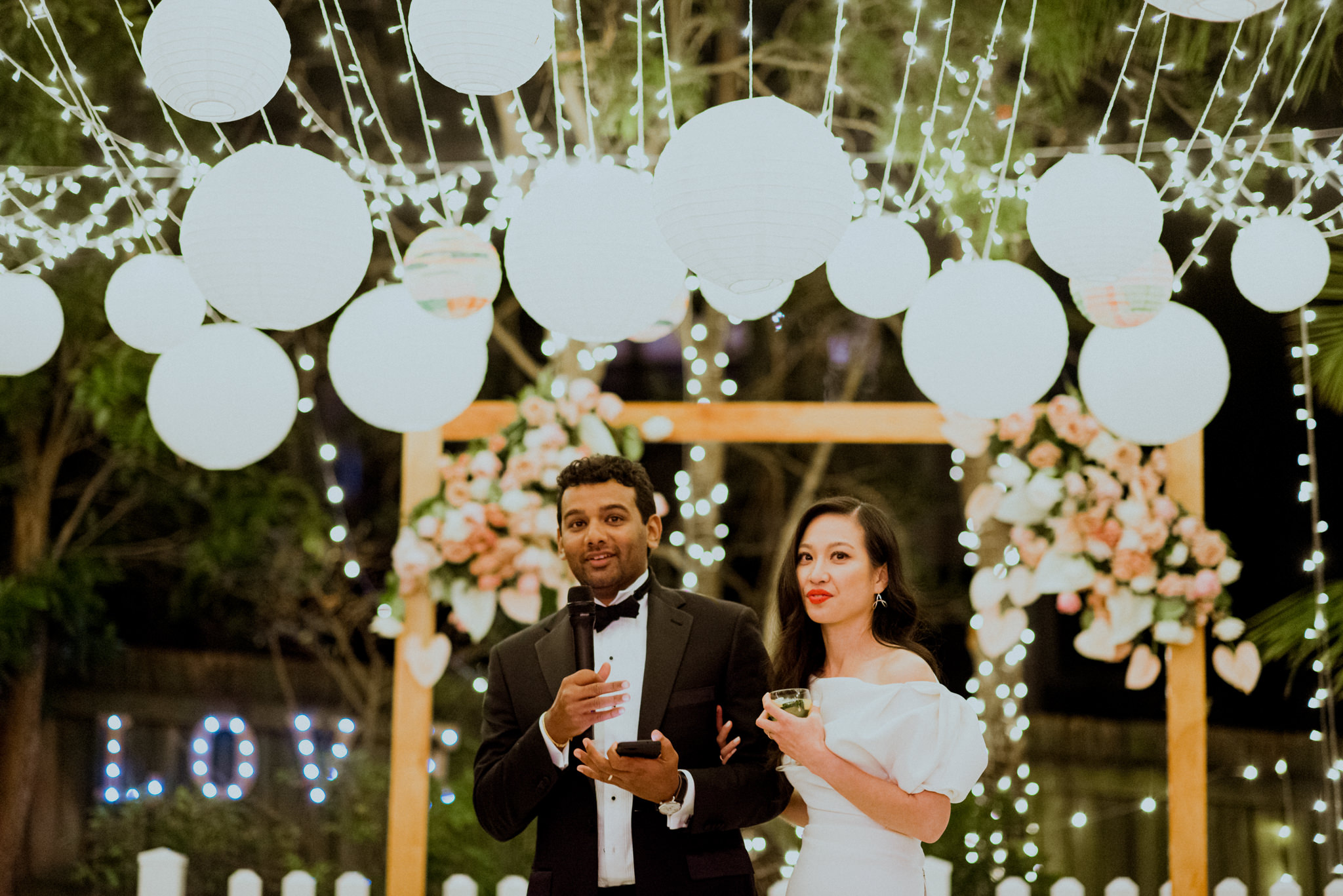 Bride and groom delivering speech underneath white lanterns