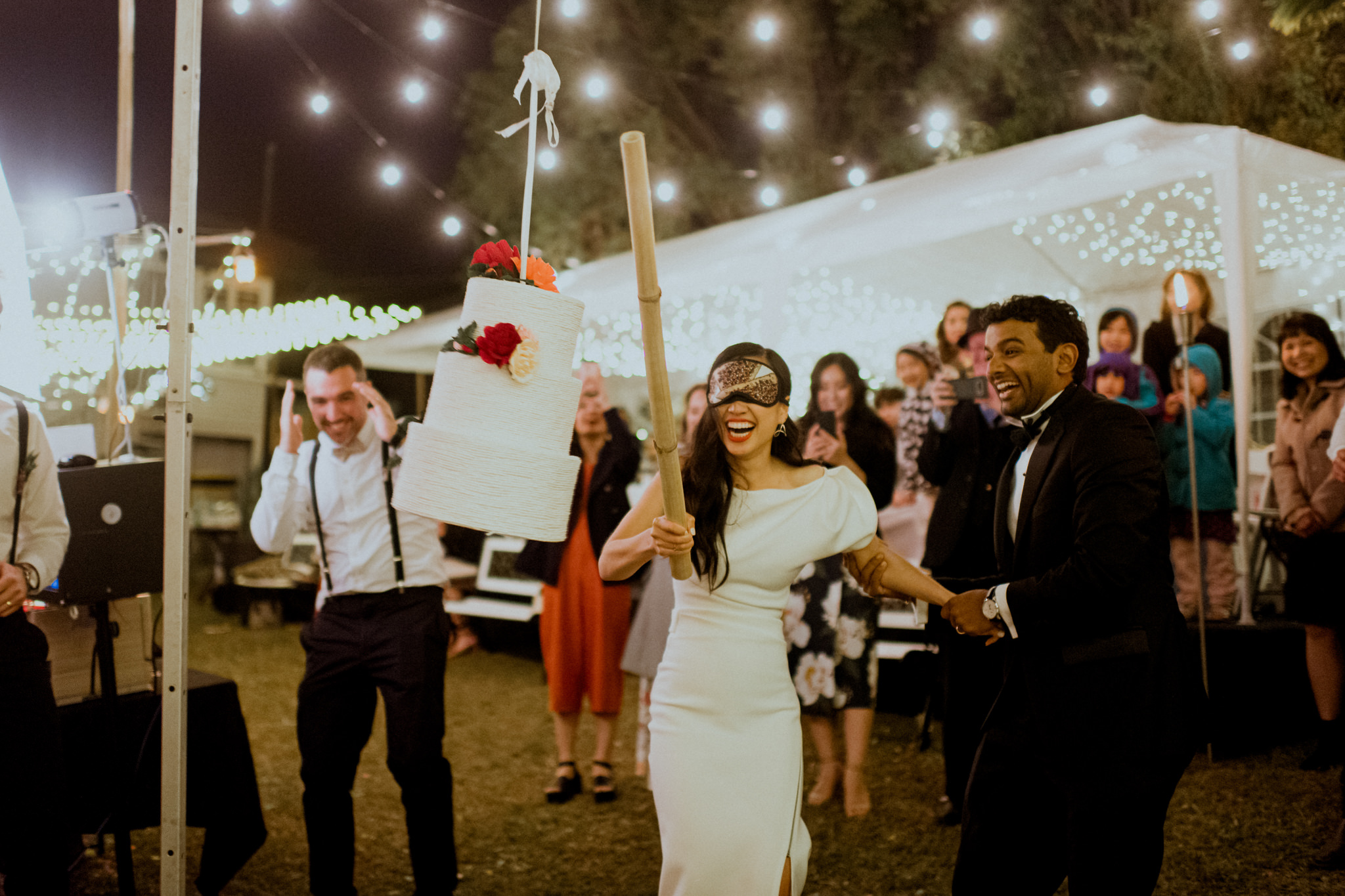 Blindfolded bride holds up a bat and attempts to hit pinata cake