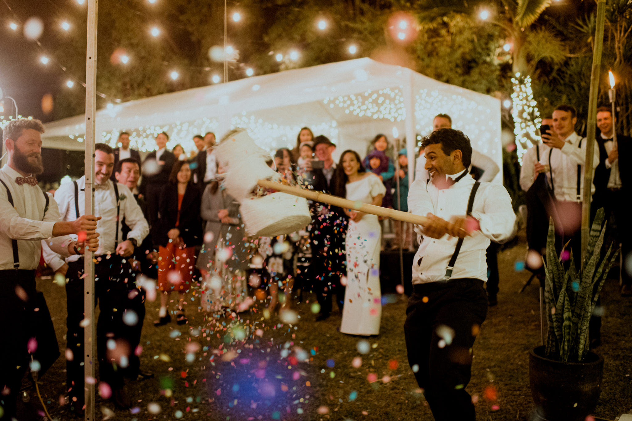 Confetti showers out of a pinata as groom hits it with a bat