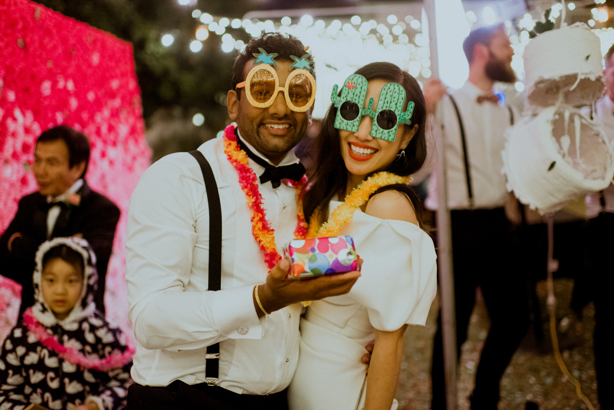 Bride and groom posing with novelty party accessories
