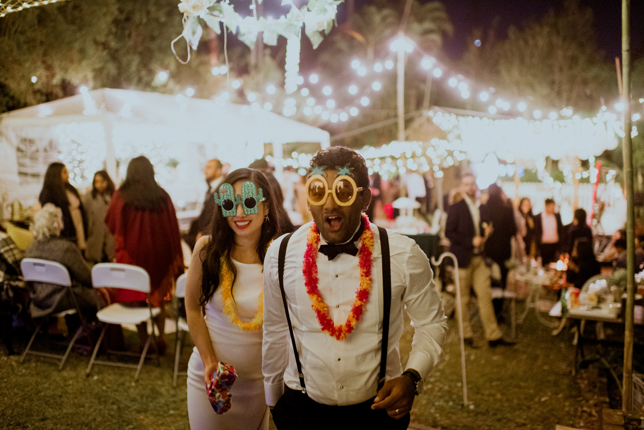 Bride and groom wearing novelty party accessories walk excitedly