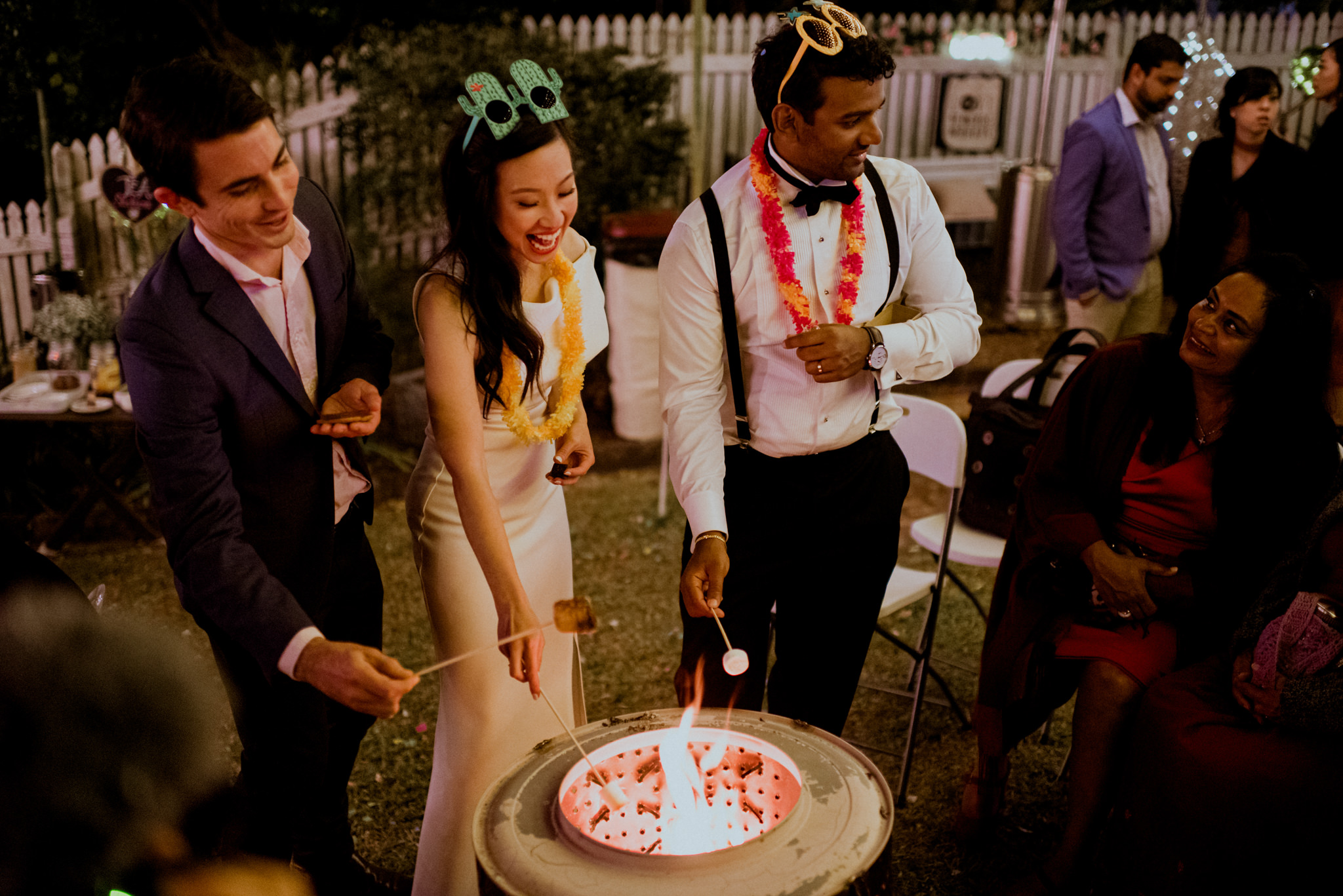 Bride and groom wearing novelty party accessories toast marshmallows in a fire pit