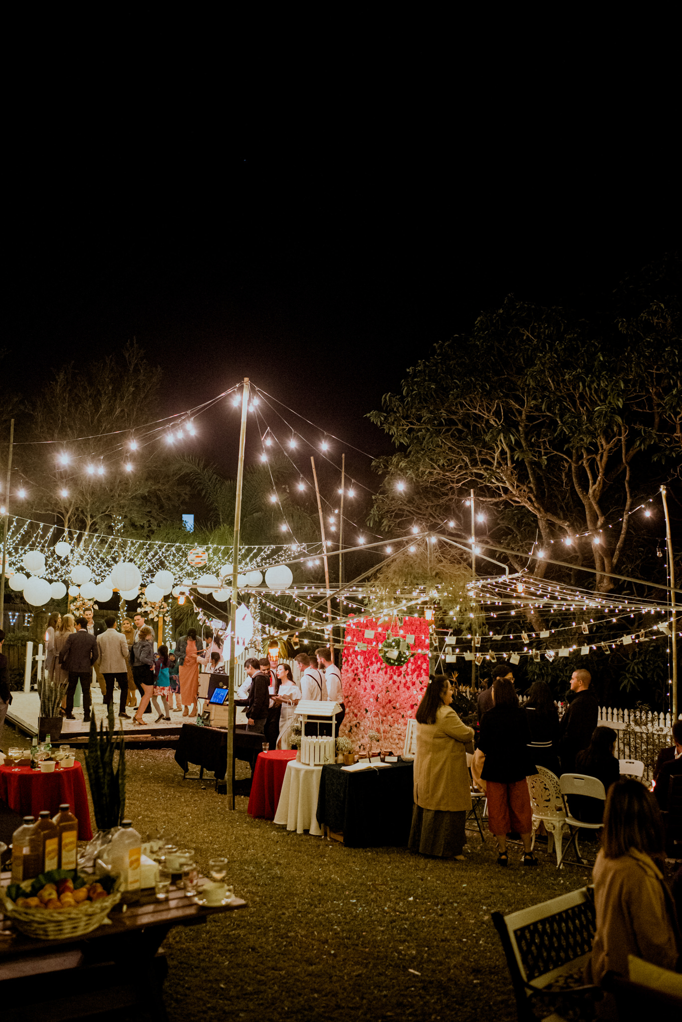 Guests dance and celebrate at a nighttime backyard wedding