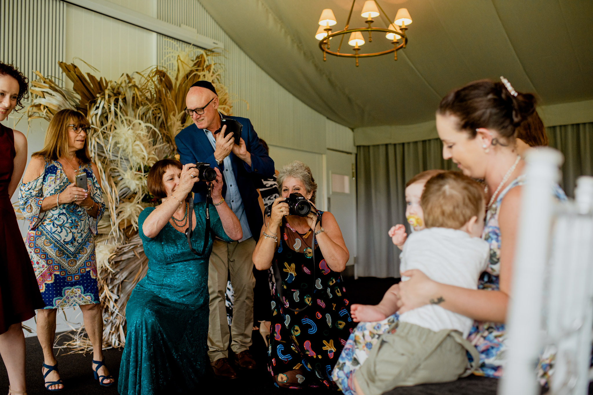 Three elderly people take photos of a young family