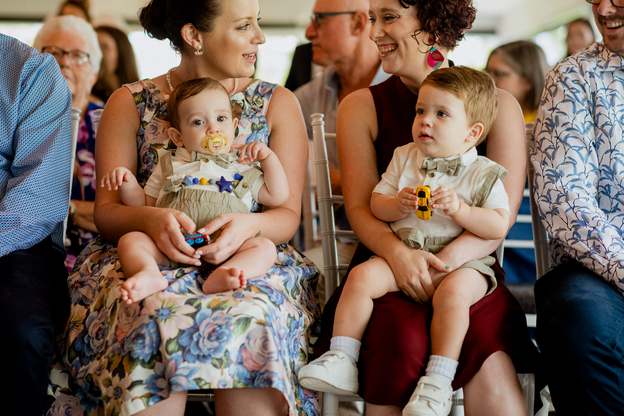 Two toddler boys sit on their mothers laps at a wedding