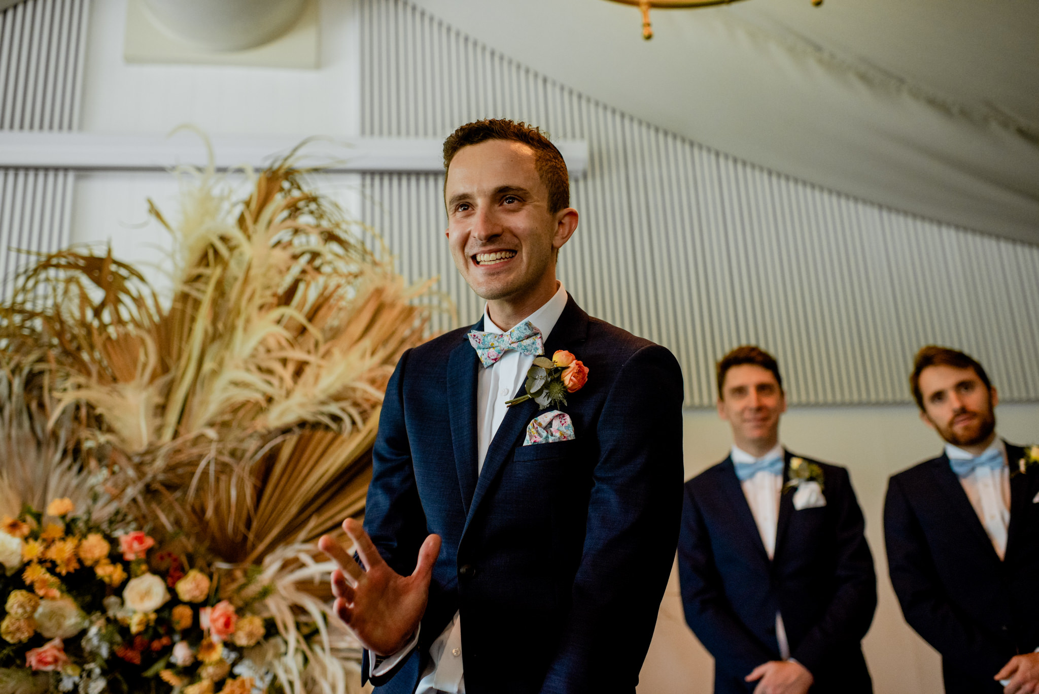 Groom smiles and waves during wedding ceremony
