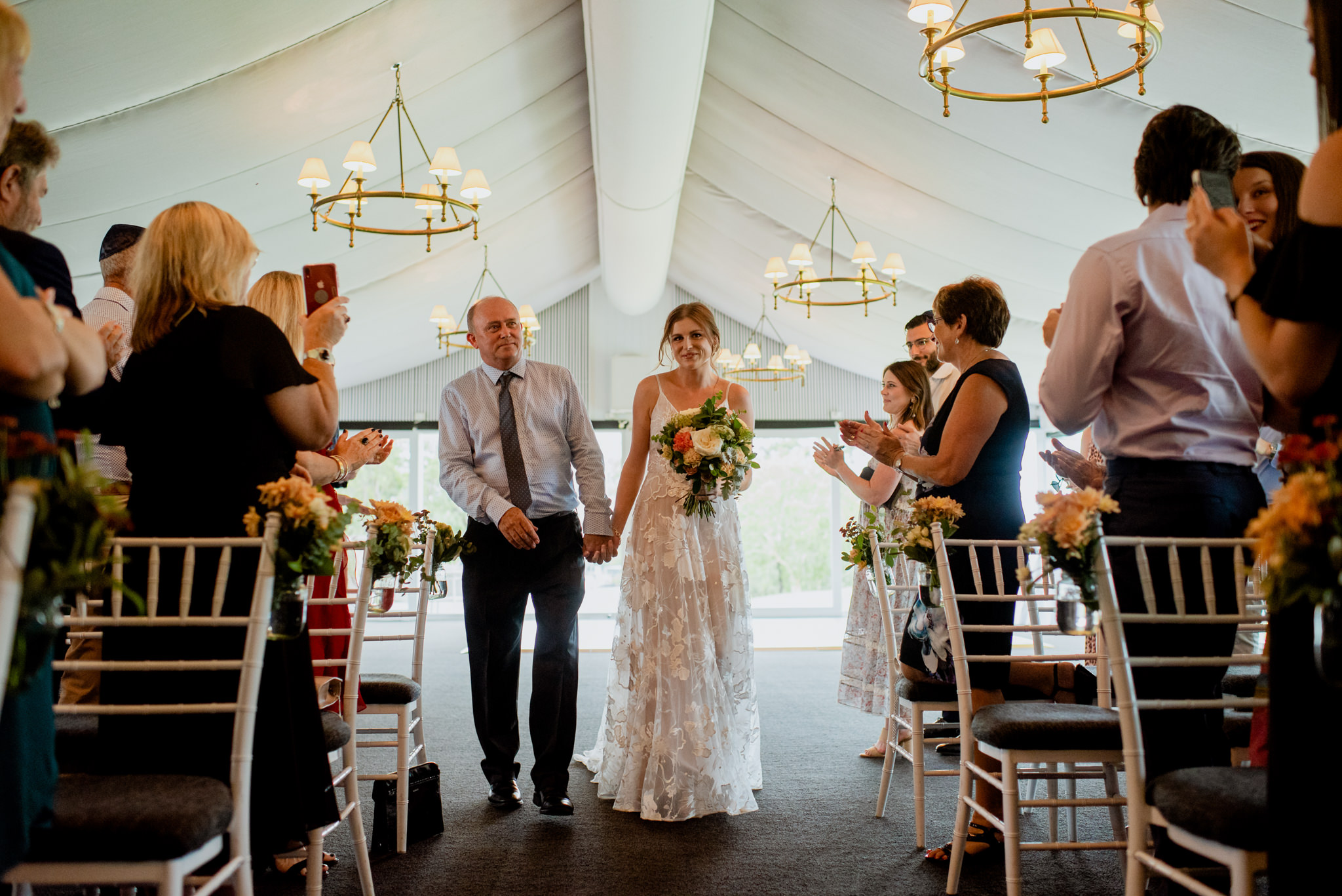 Bride and father walk down the aisle with guests applauding