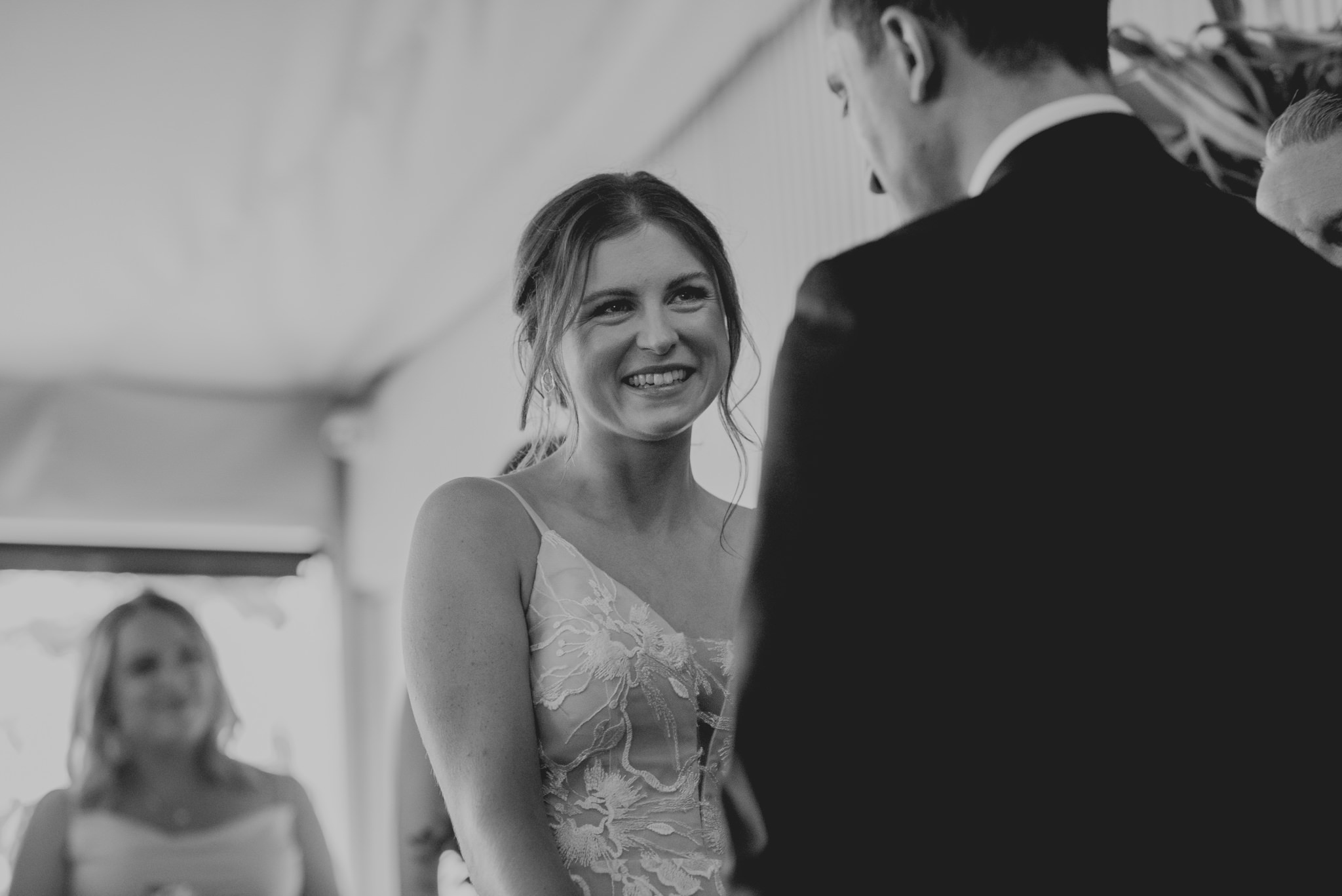 Bride smiles and laughs at husband-to-be during wedding