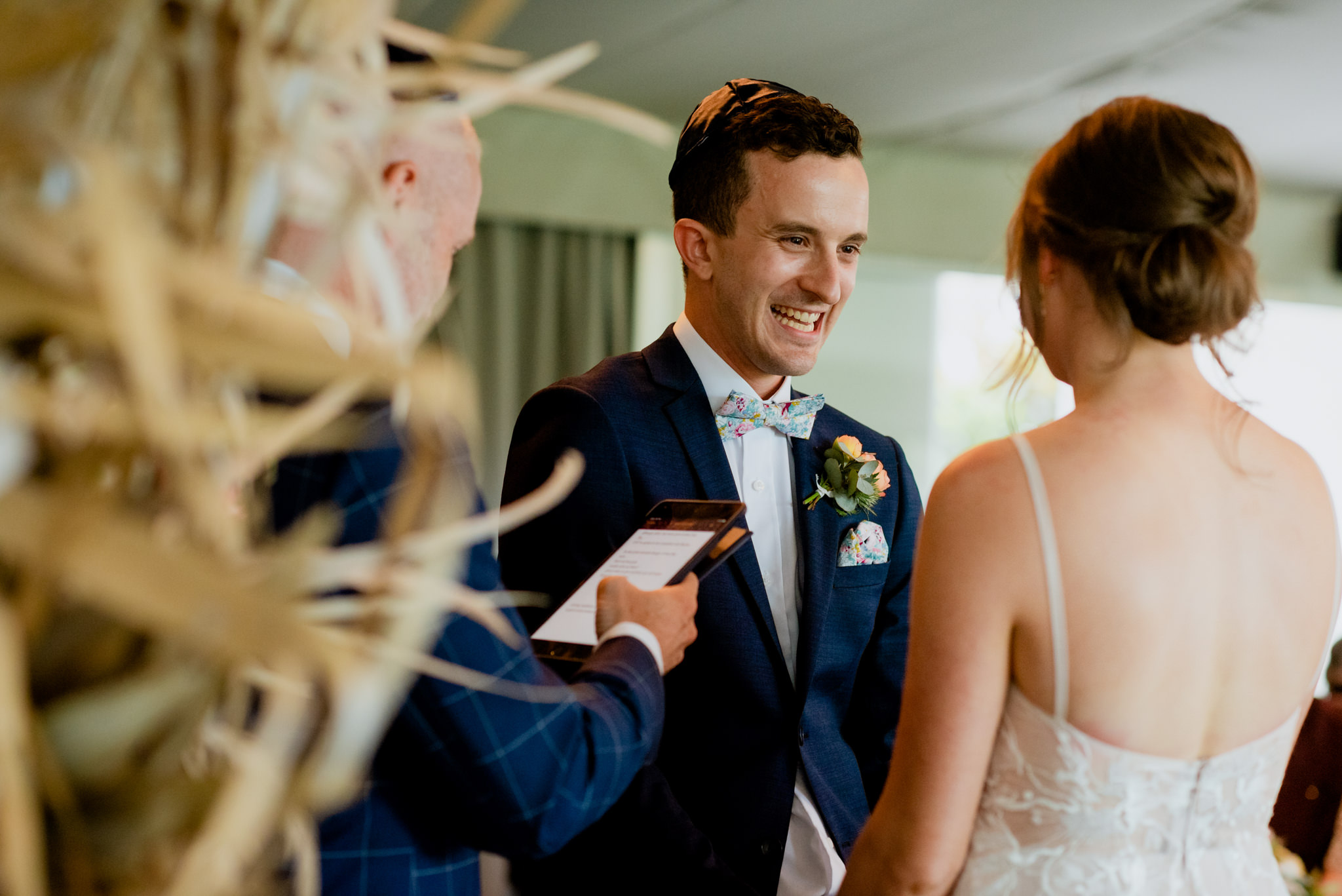 Groom smiles and laughs nervously at wife-to-be during wedding
