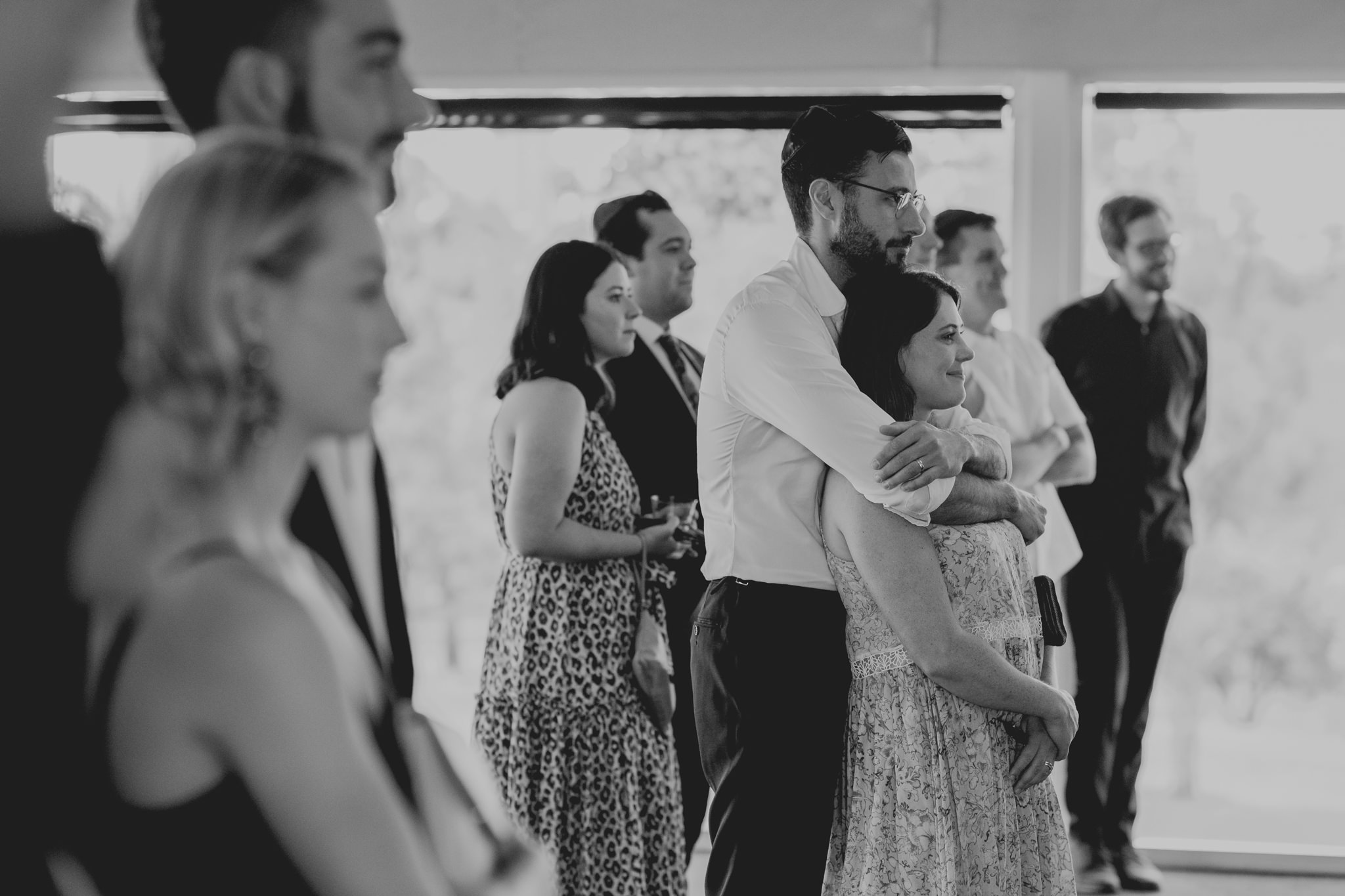 Two guests hug each other as they watch a wedding