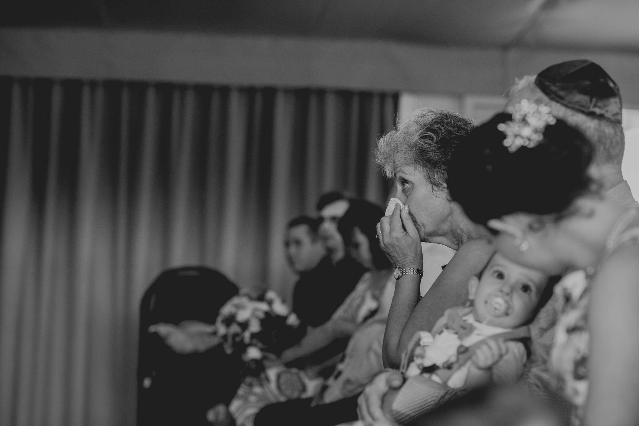 Mother of the groom wipes her nose during a wedding