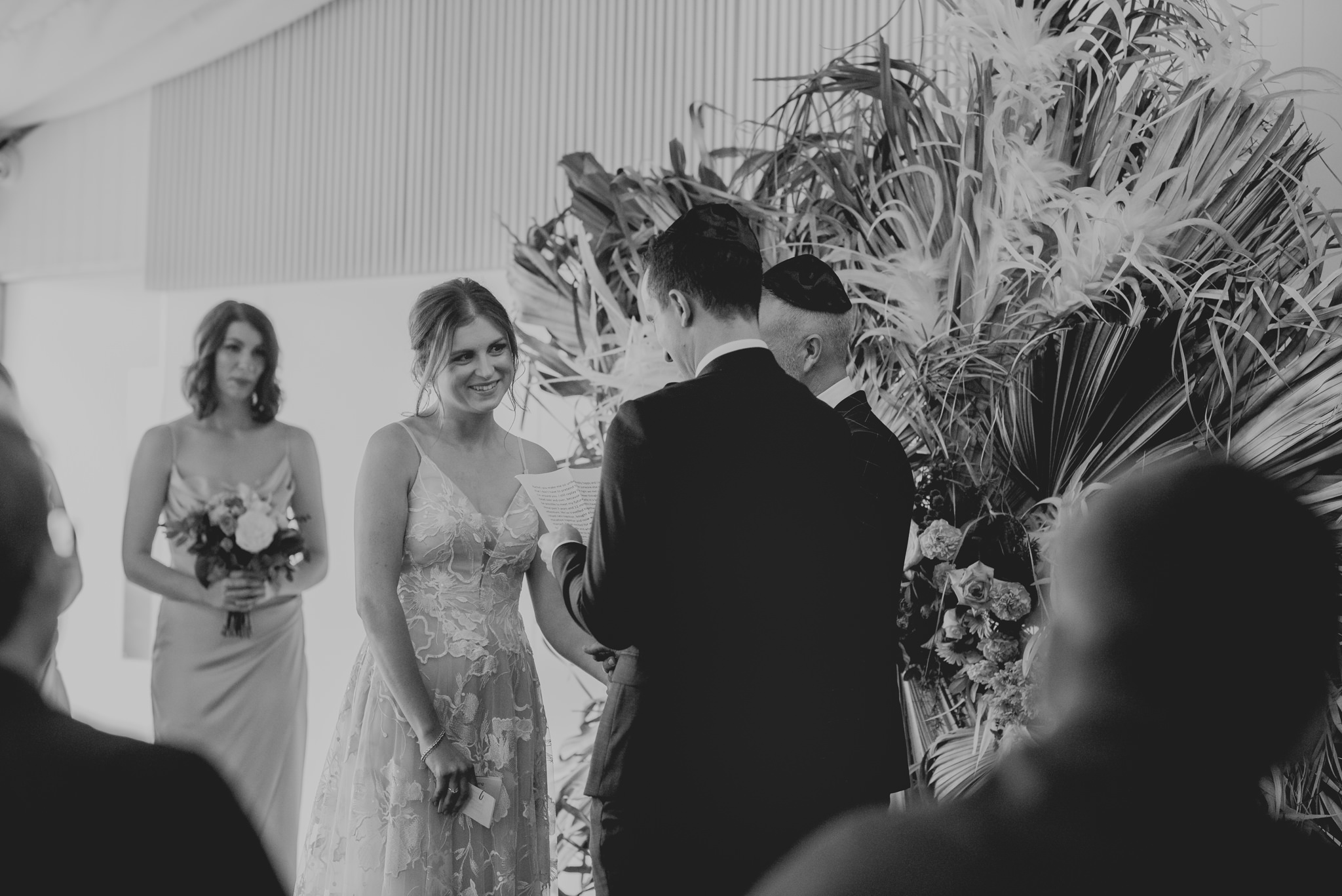 Bride smiles as she receives her ring during her wedding