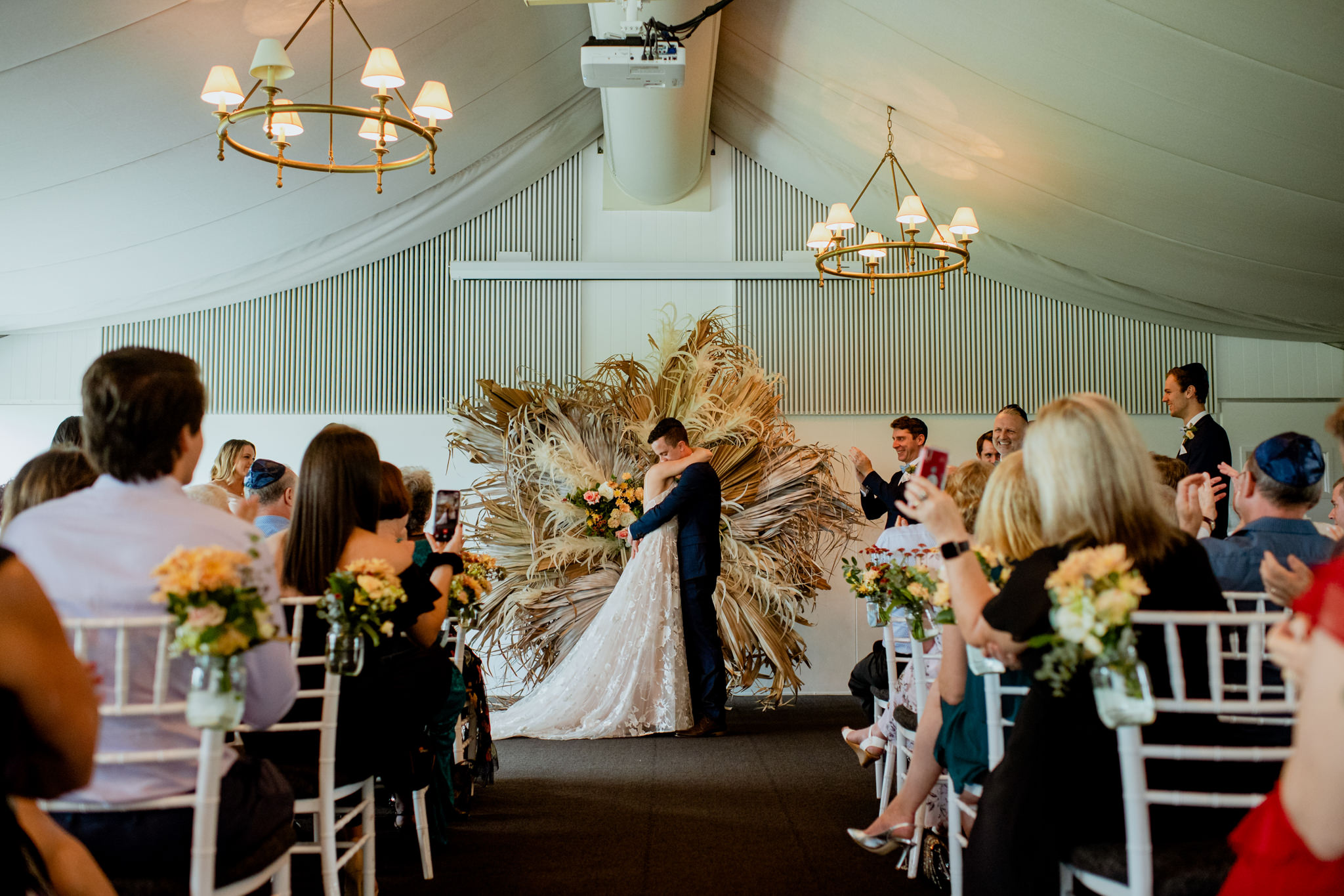 Bride and groom hug after sharing their first kiss