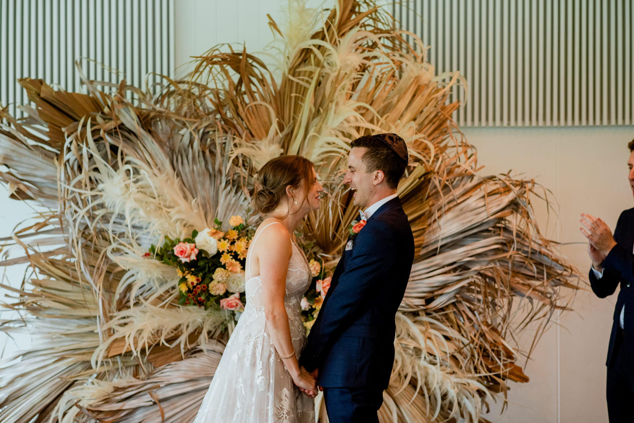 Bride and groom laugh after sharing their first kiss