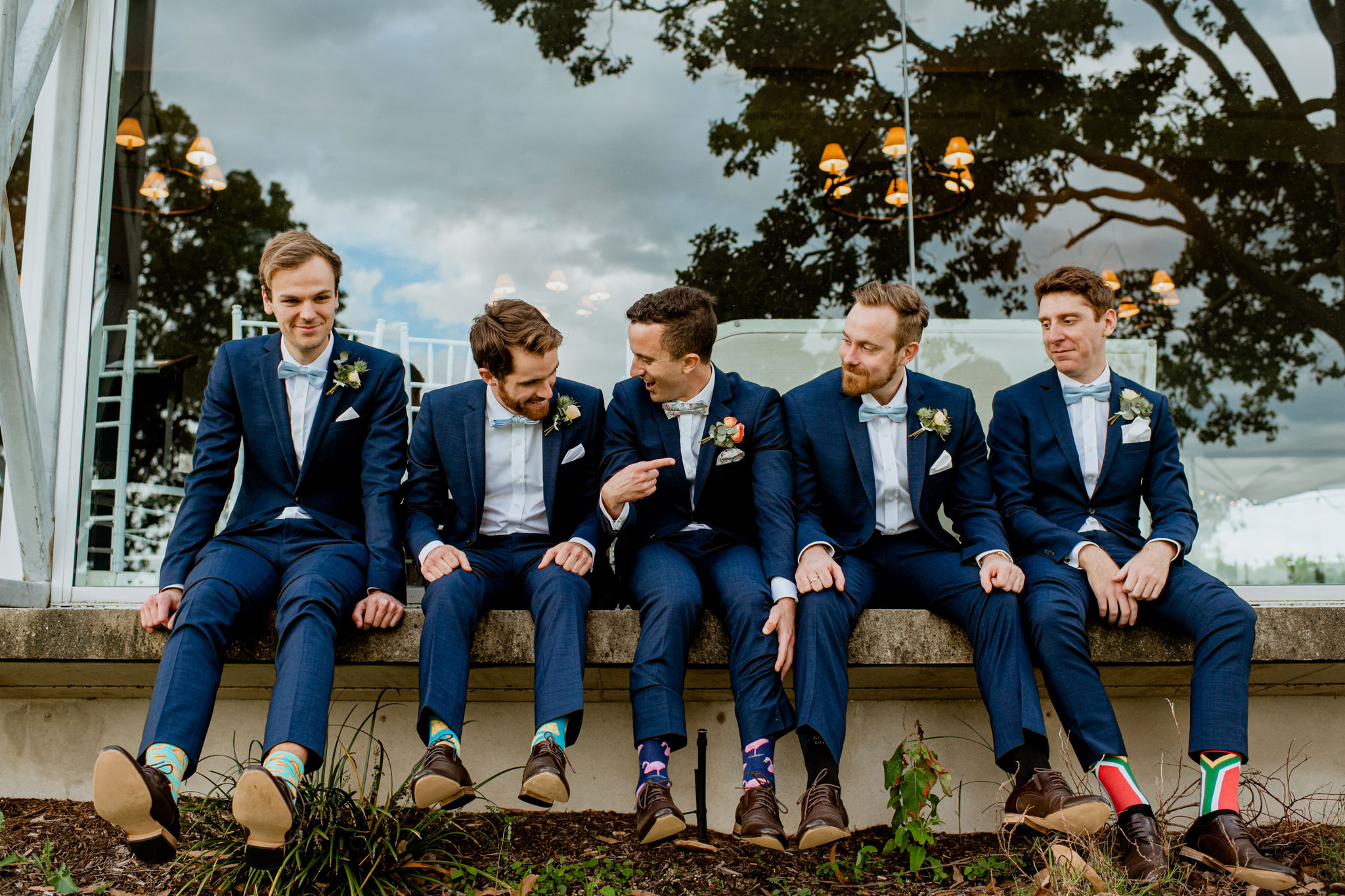 Groomsmen with groom sitting in a row showing their socks
