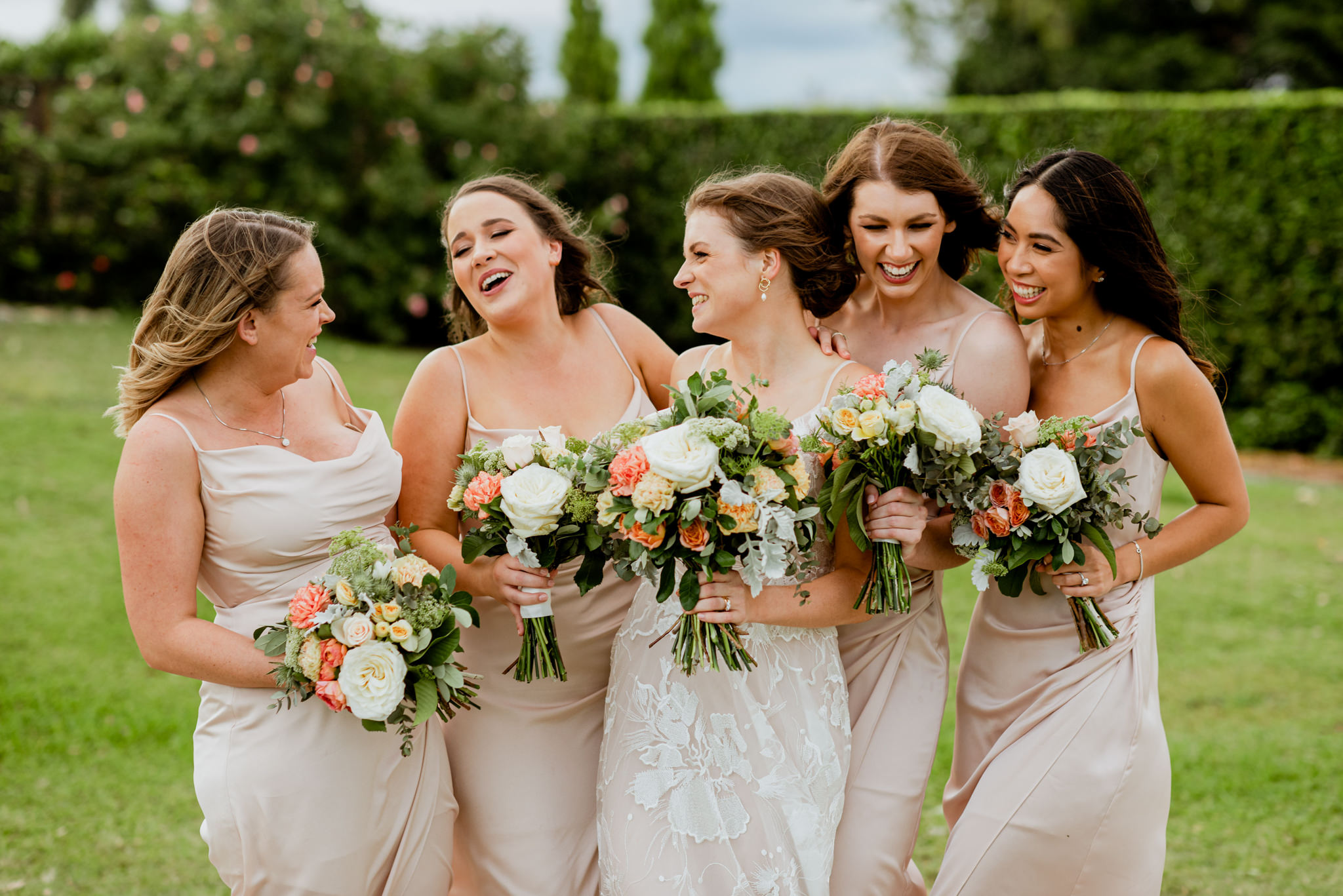 Bridesmaids and bride together in a line laughing