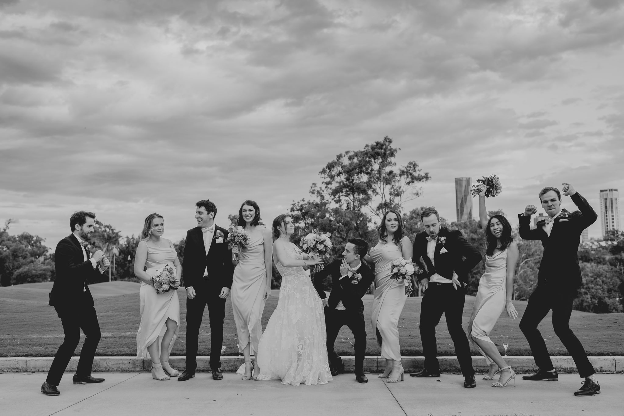 A bridal party dancing together on a golf course in front of a city skyline
