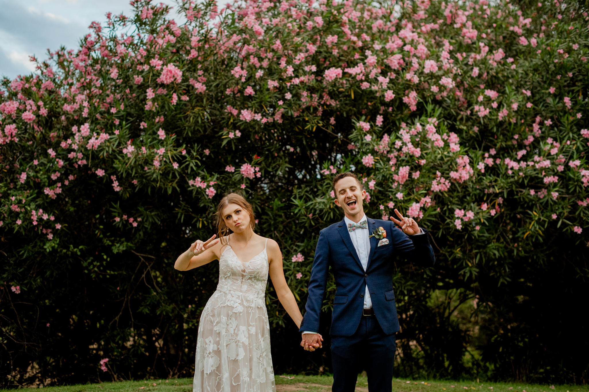 A newly married bride and groom making cute poses in front of a pink flower bush