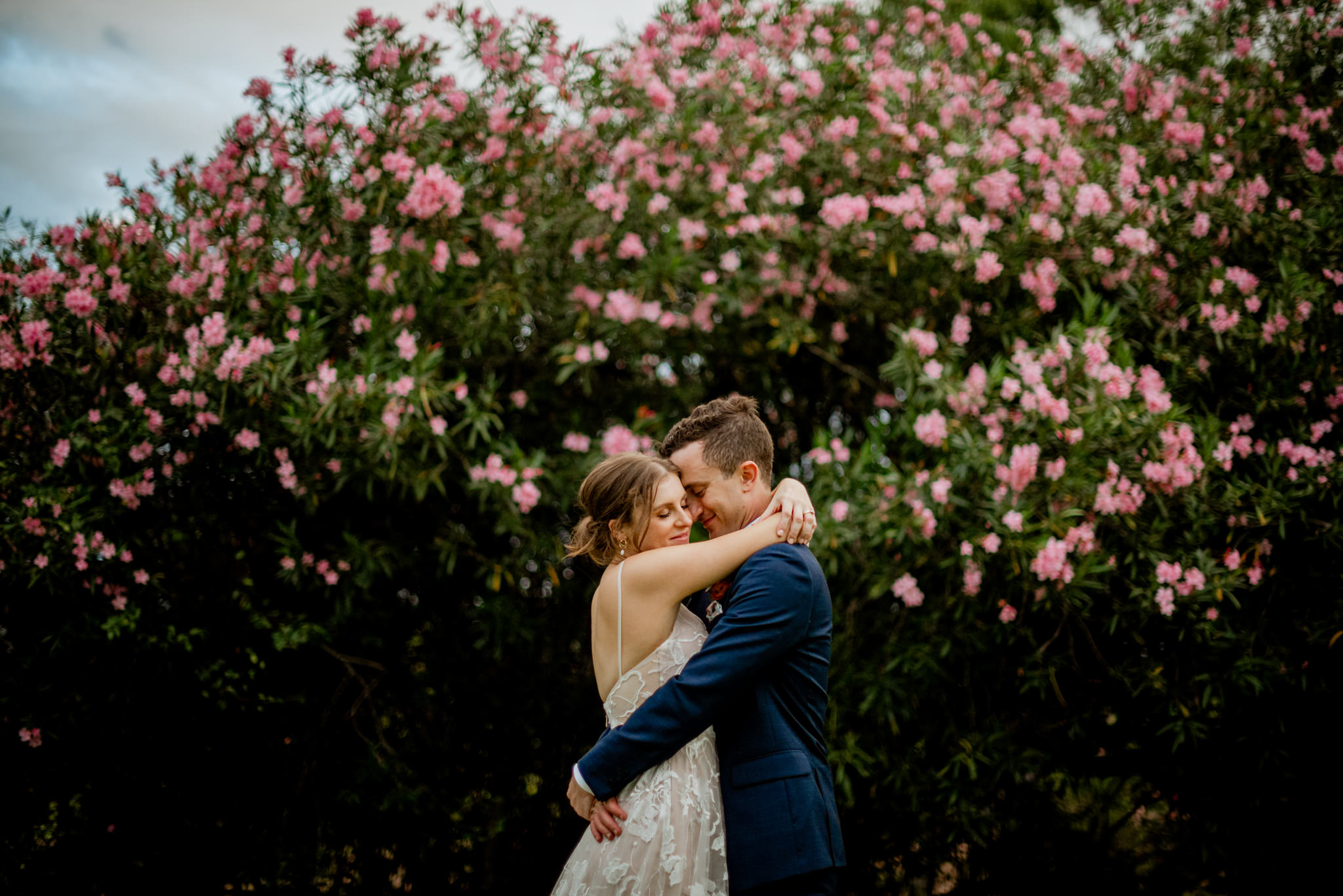 A newly married bride and groom hugging in front of a pink flower bush