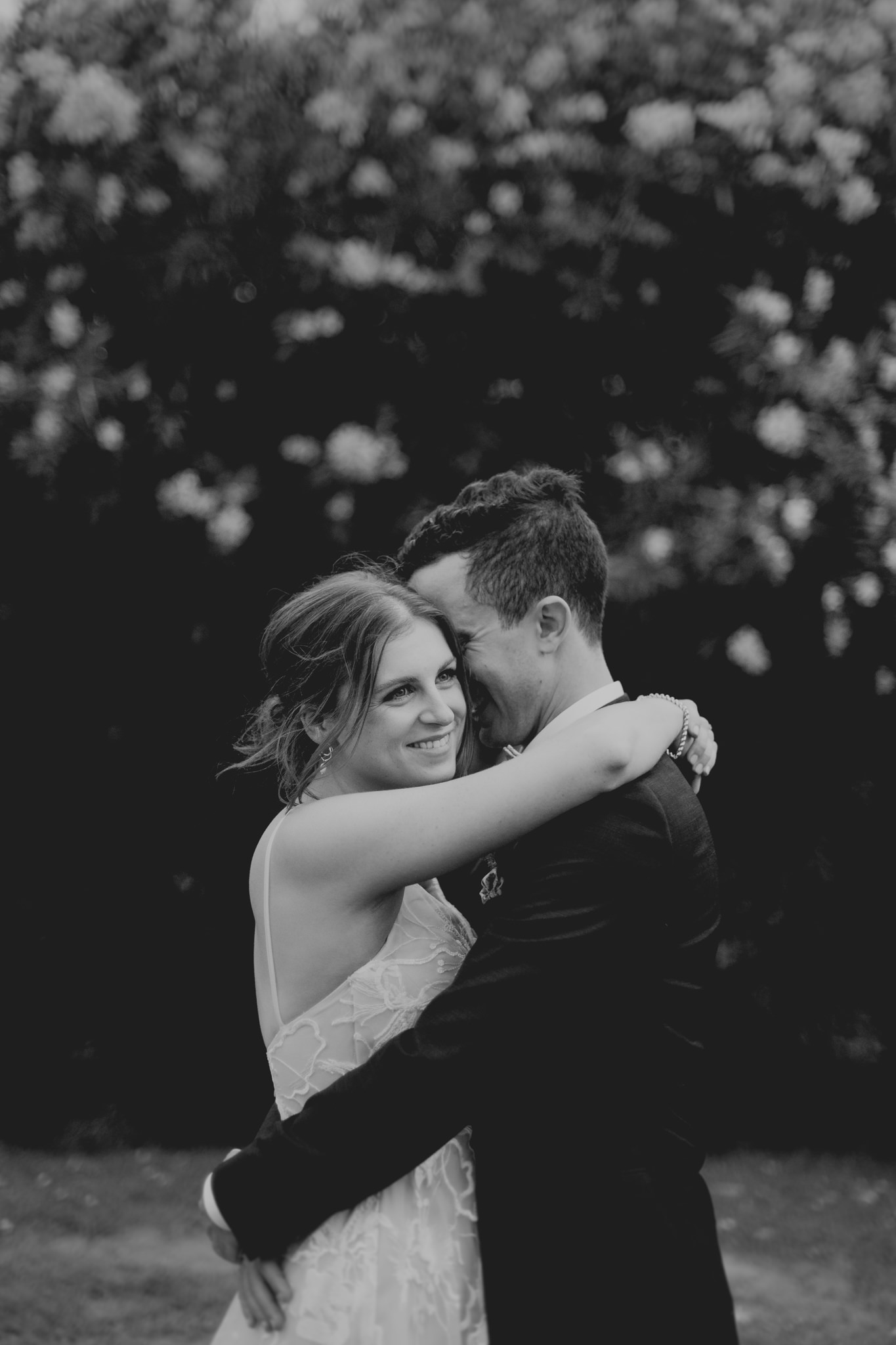 A newly married bride smiles as she hugs her groom