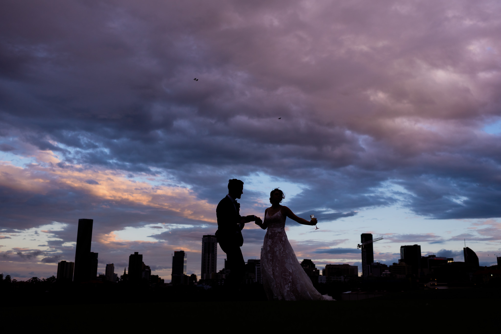 Silhouette of a couple dancing in front of a city skyline under a blue and purple cloudy sky