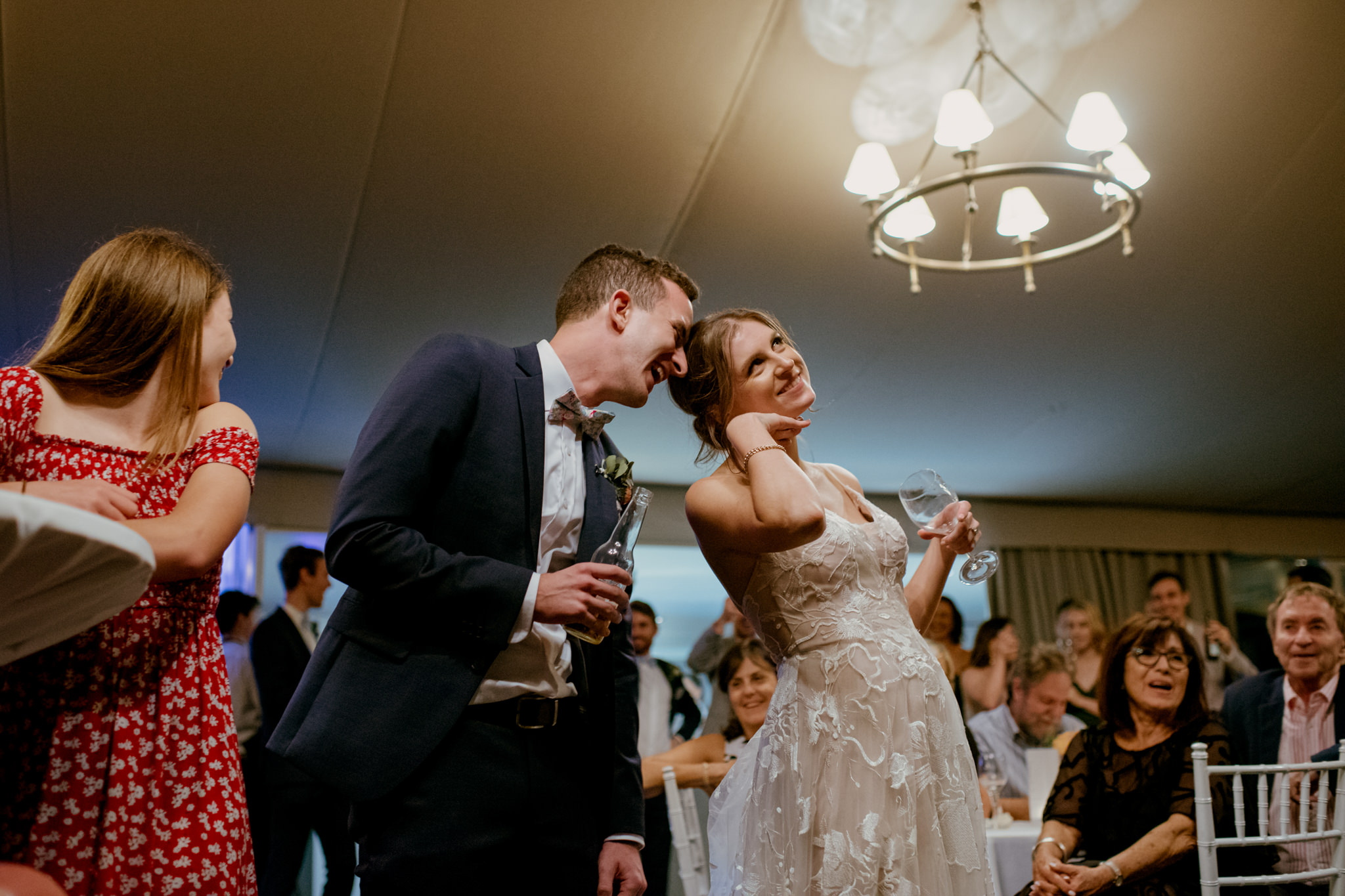Bride with cute pose and groom laughing with her