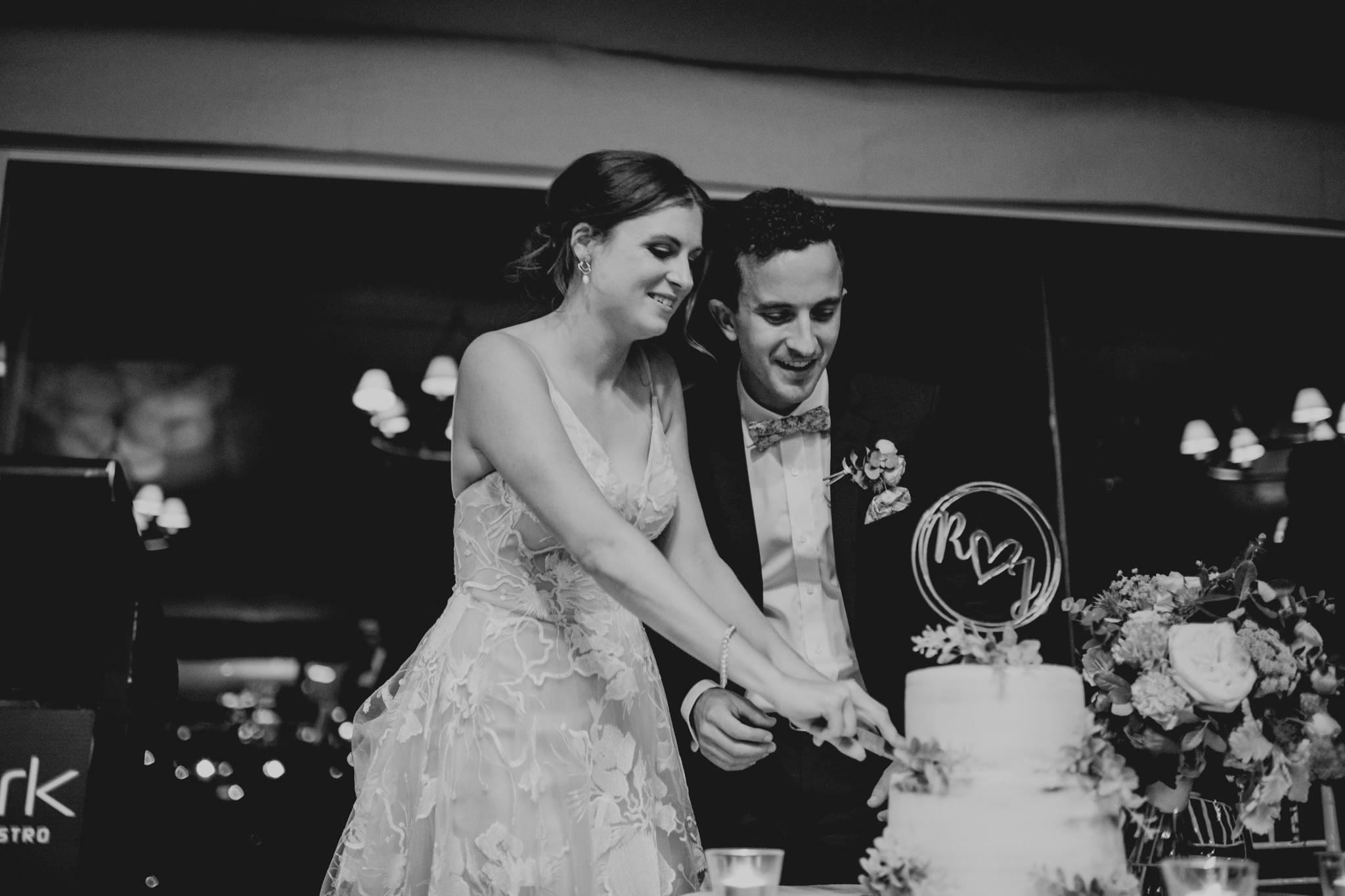 Bride and groom enthusiastically cut wedding cake