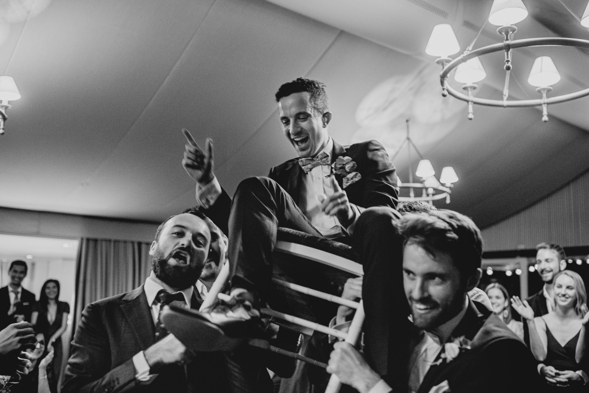 Groom sitting on a chair being carried by several other men