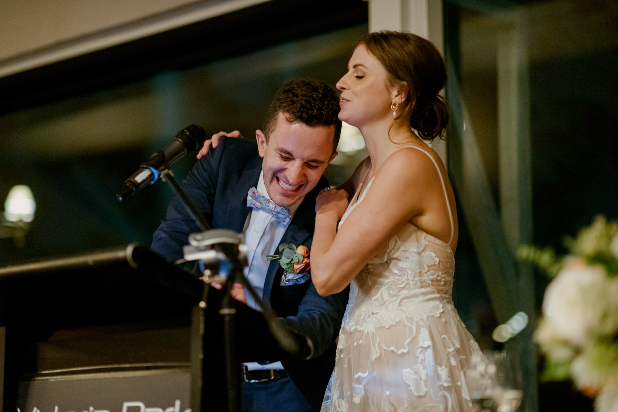 Groom laughing and crying while delivering wedding speech being comforted