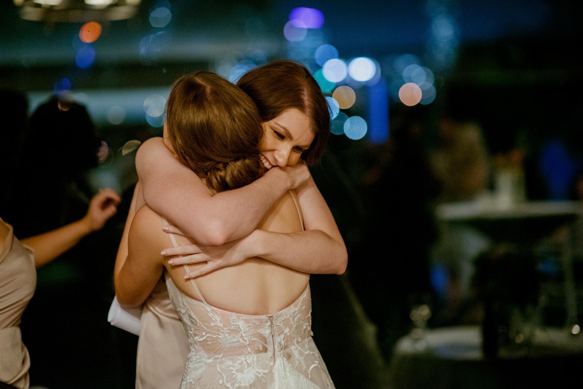 Bridesmaid emotionally hugging bride