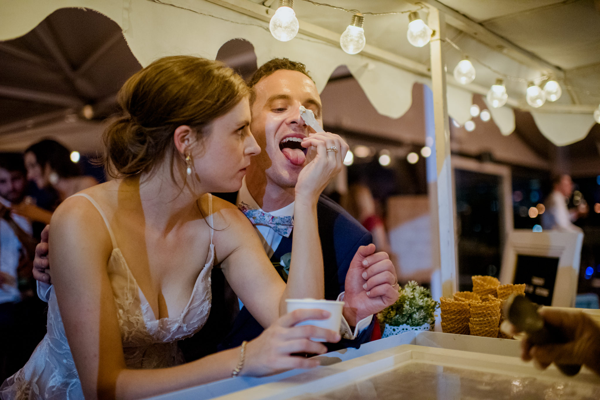 Bride playfully smearing ice cream on groom's nose