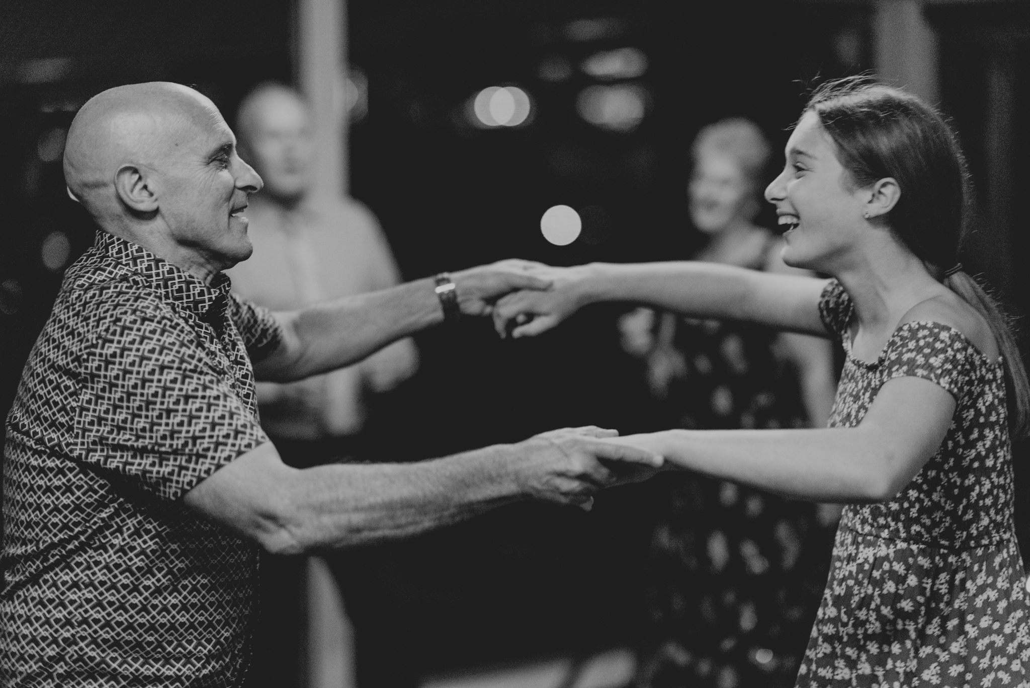 Two guests hold hands and dance at a wedding