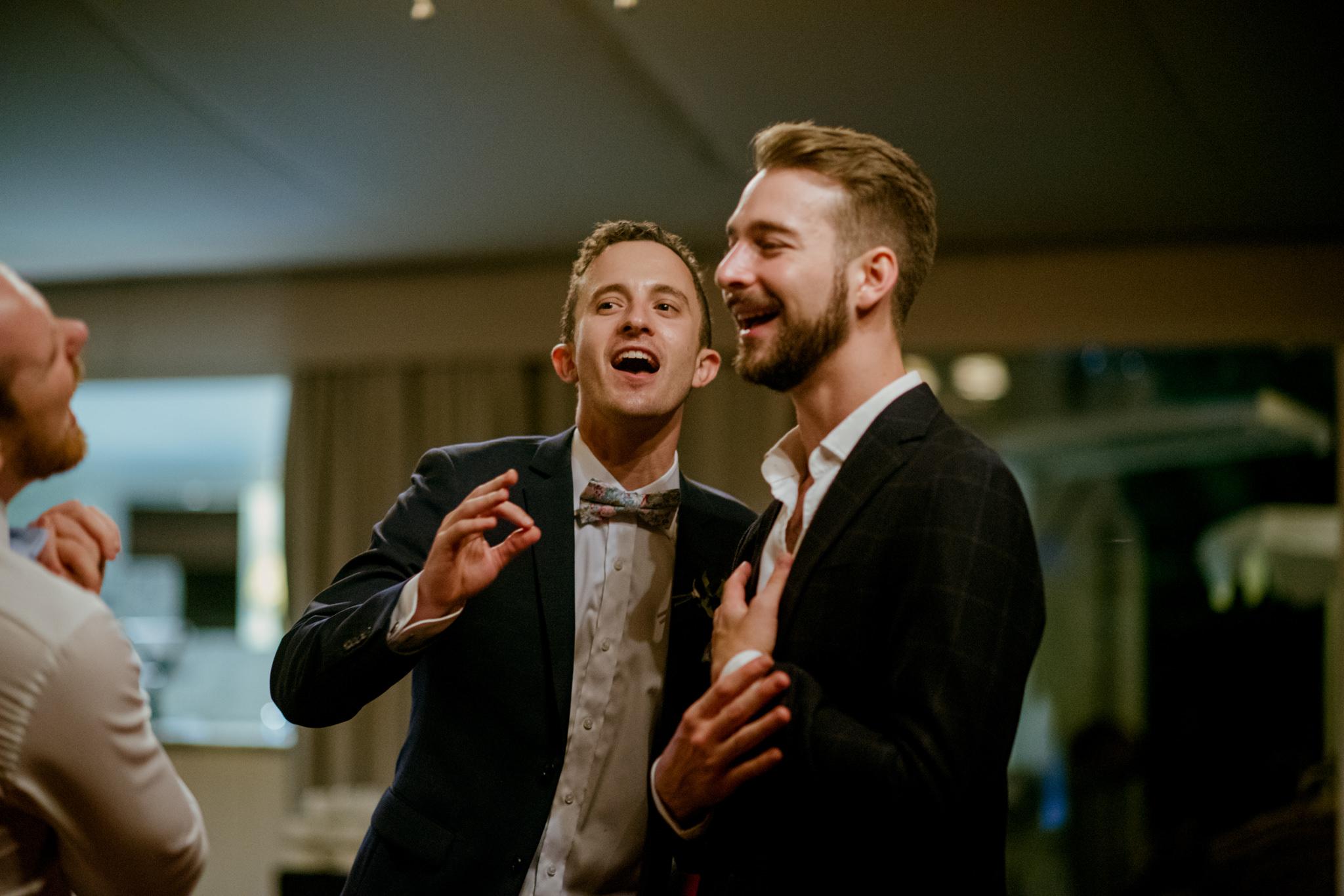 Groom and groomsman sing and dance as a wedding