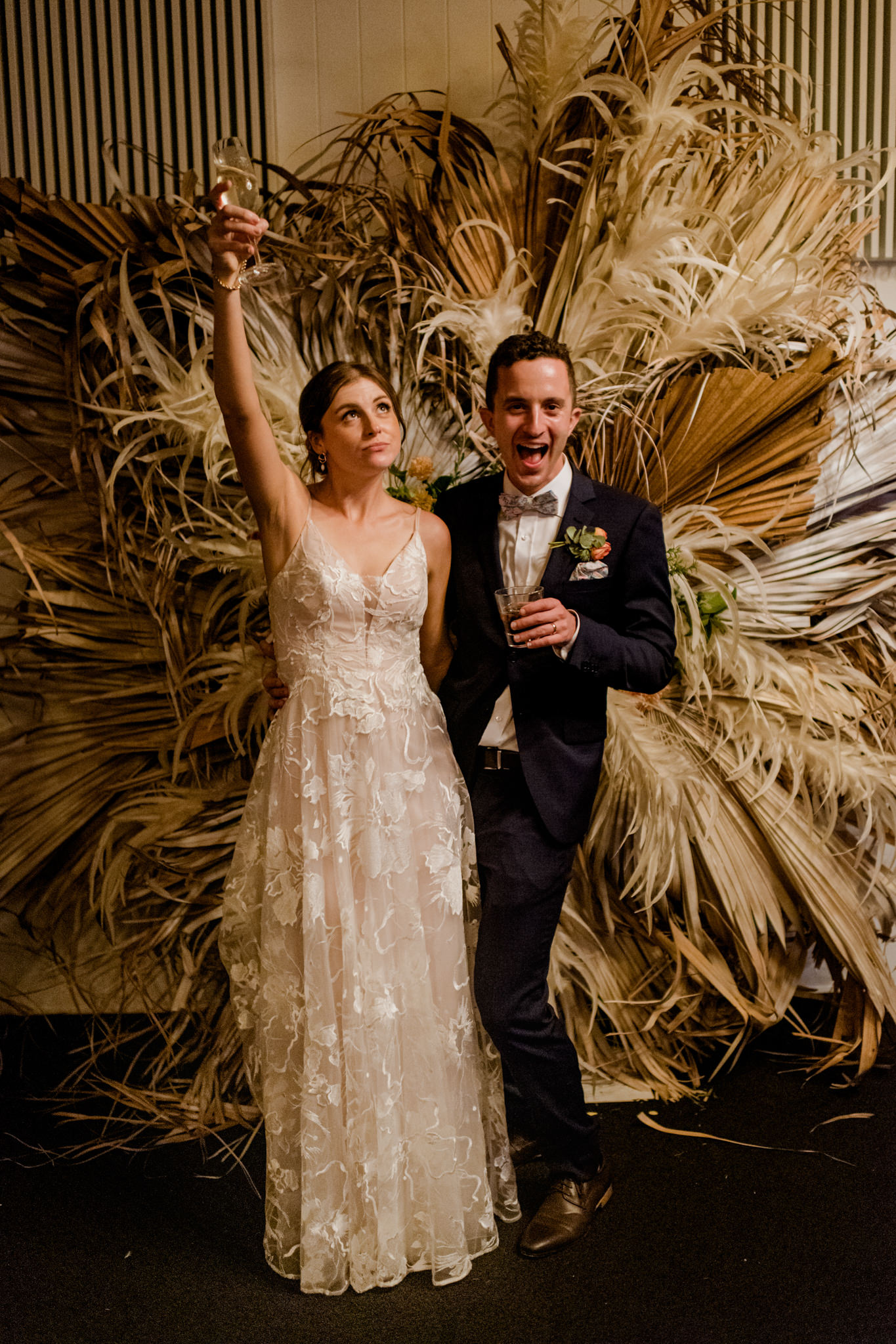 Bride and groom posing with drinks in front of a flower arbour