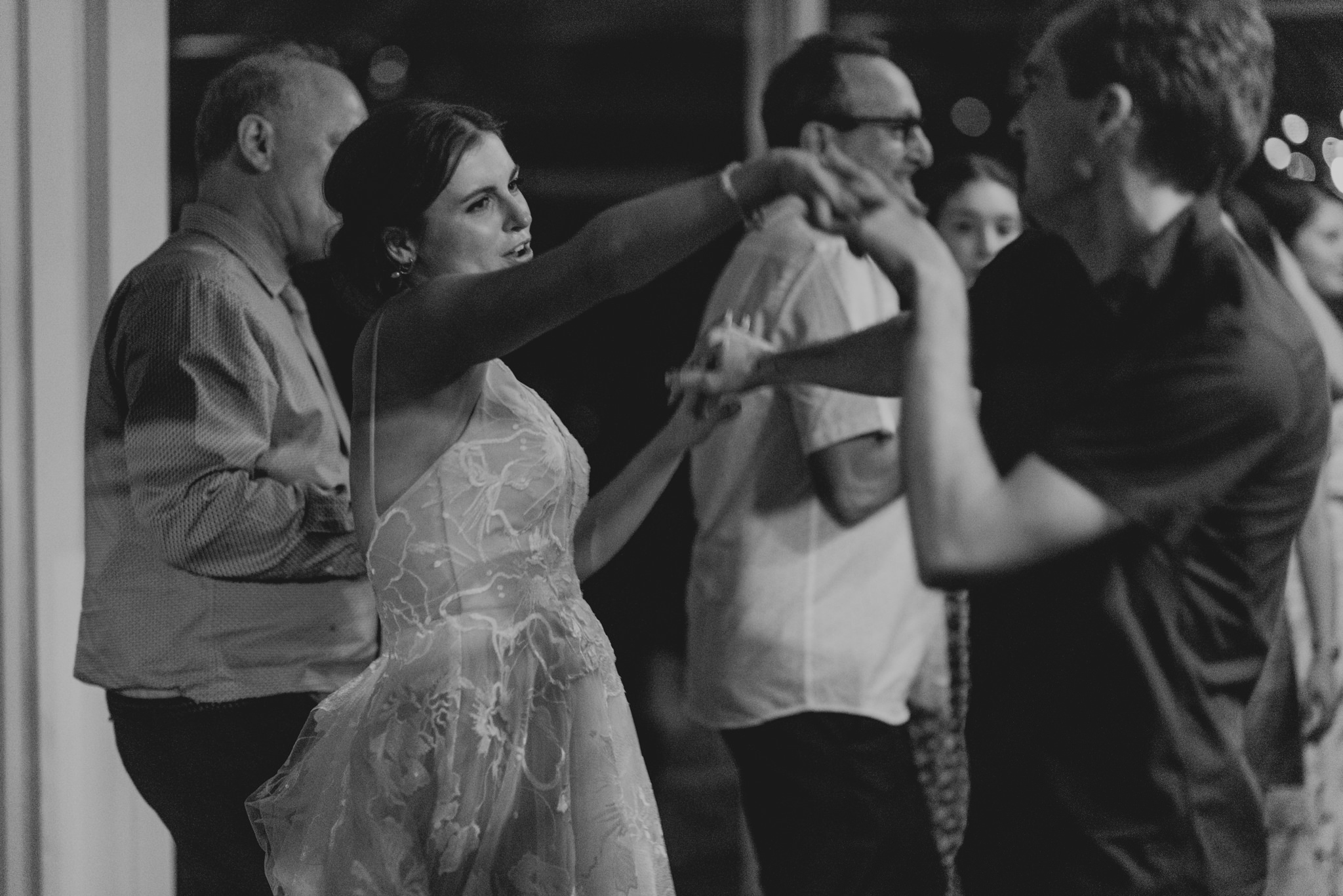 Bride holds hands with man as she dances on dancefloor