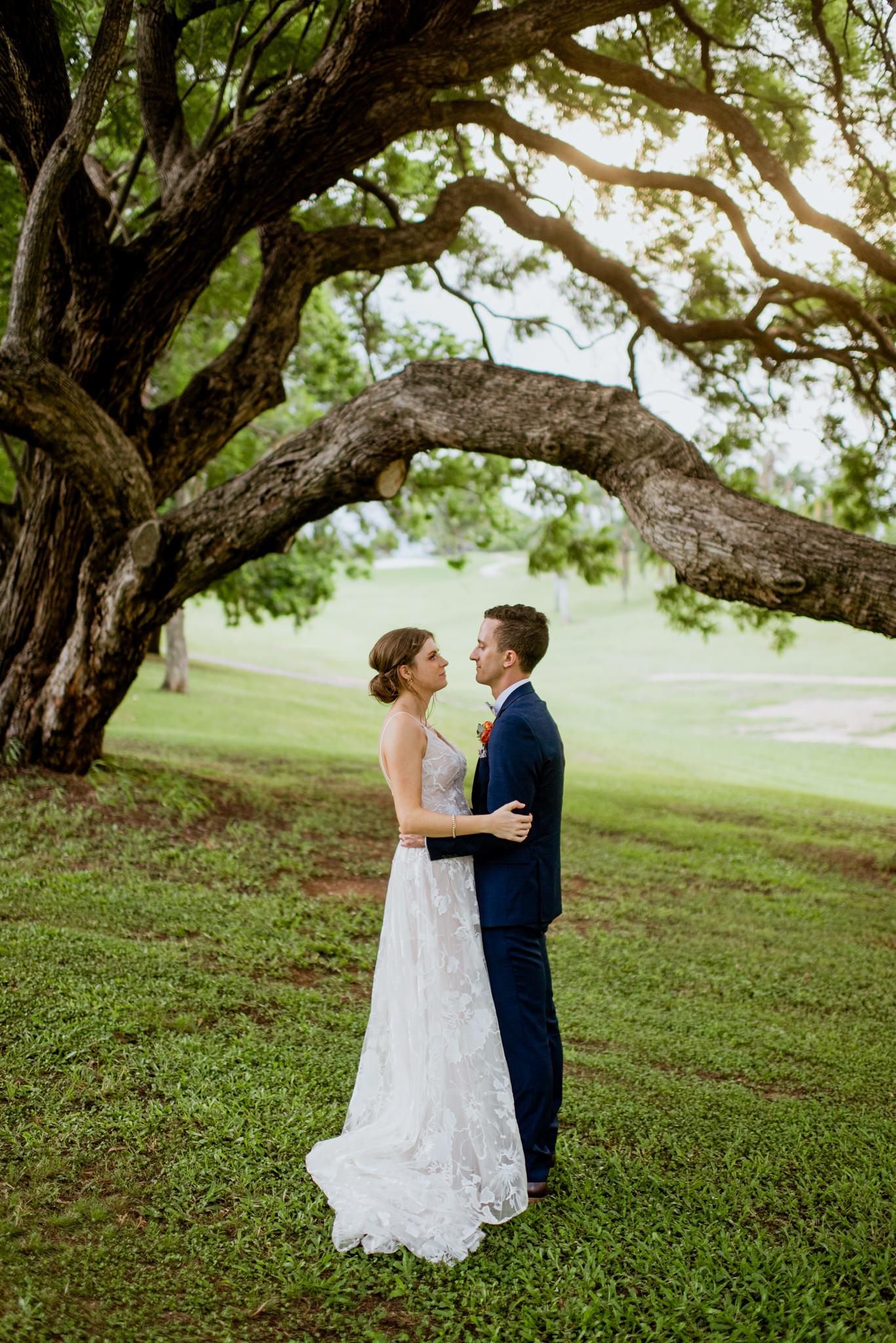 Newly married couple standing under long tree branch and staring at each other