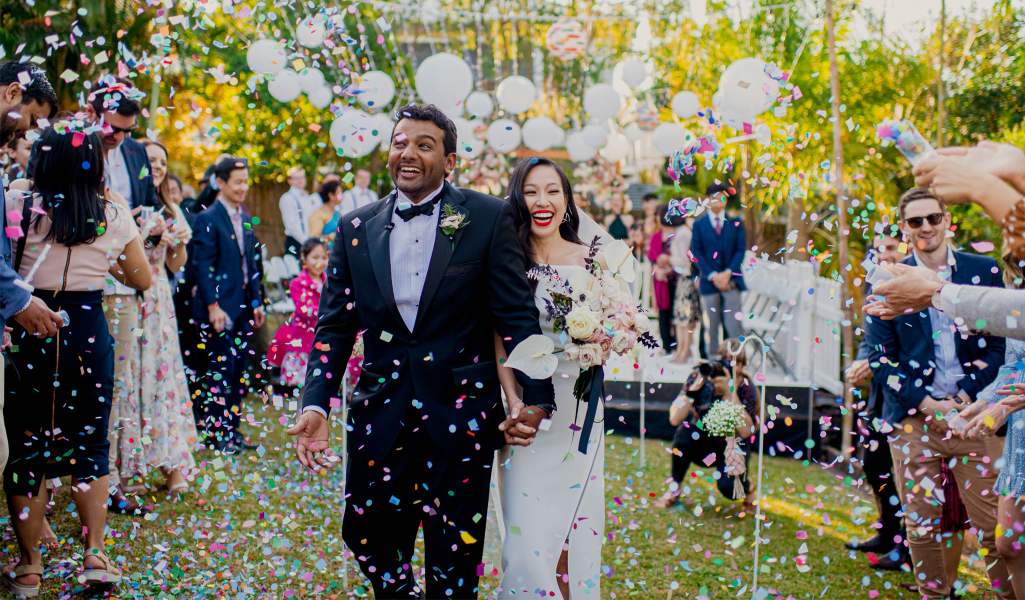 Interracial bride and groom laugh as they walk down their backyard wedding aisle through a shower of confetti