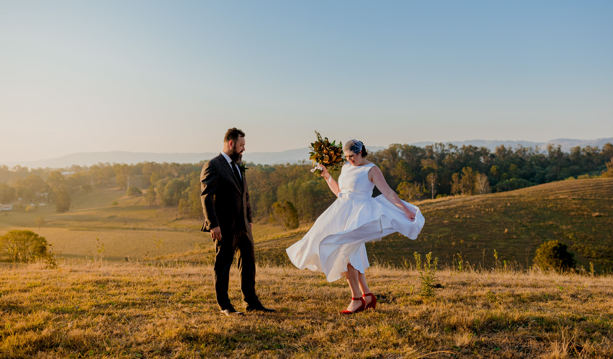Bride spins in her wedding dress on a grassy hill next to groom