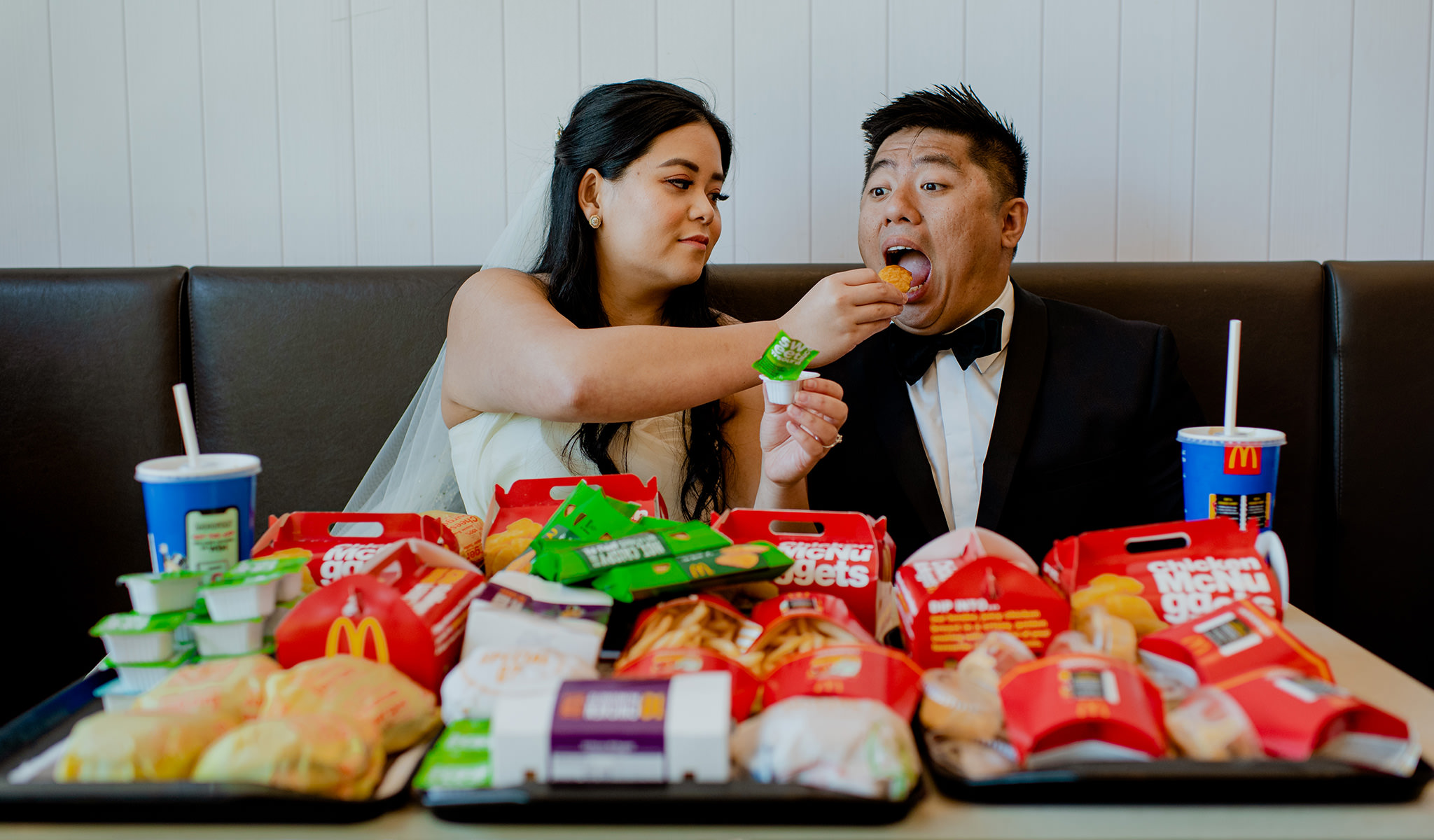 Bride feeds her husband a chicken nugget as they sit in front of tables full of fast food