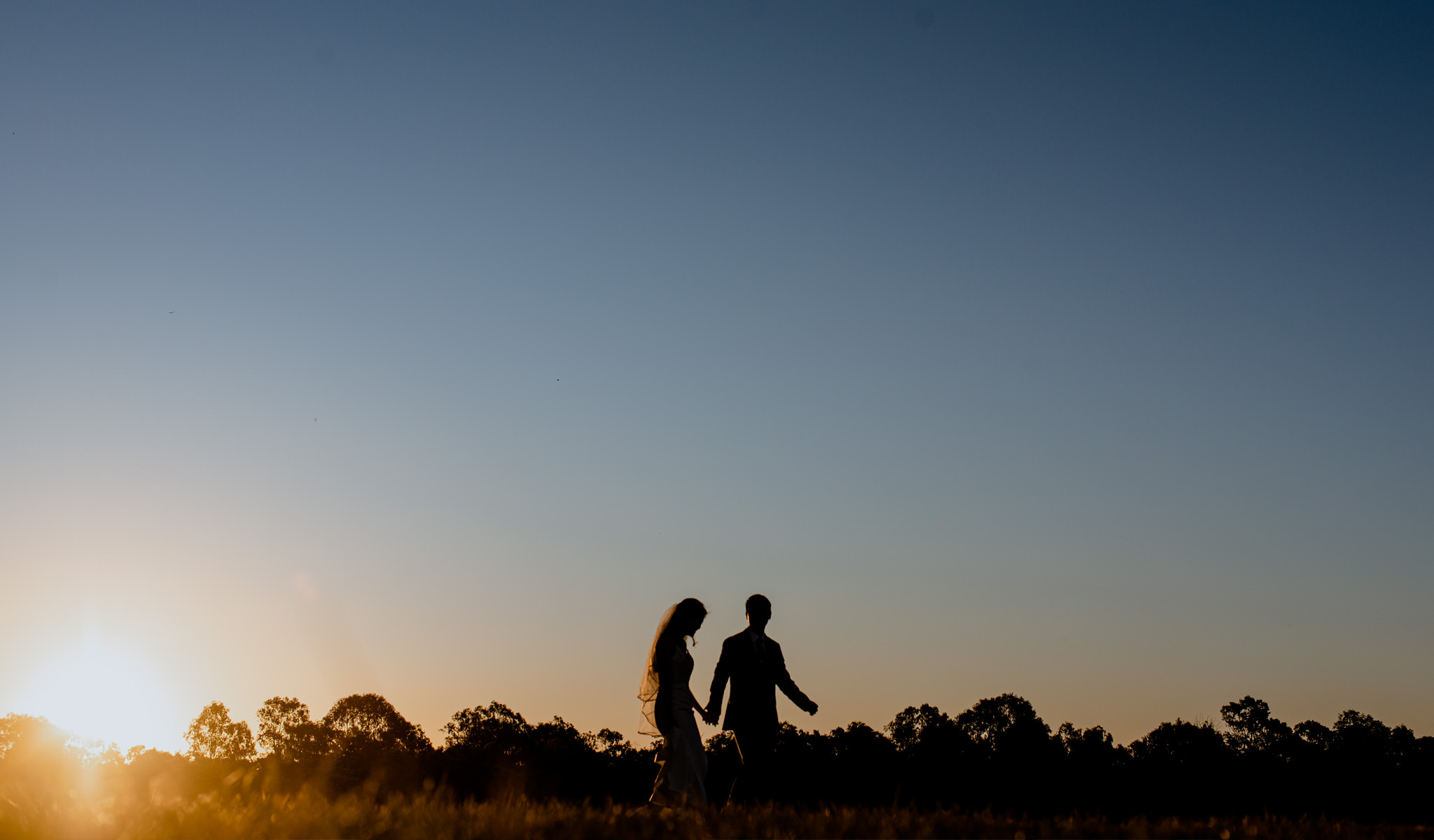 A silhouette of a man and a woman walking on an open field against a sunset