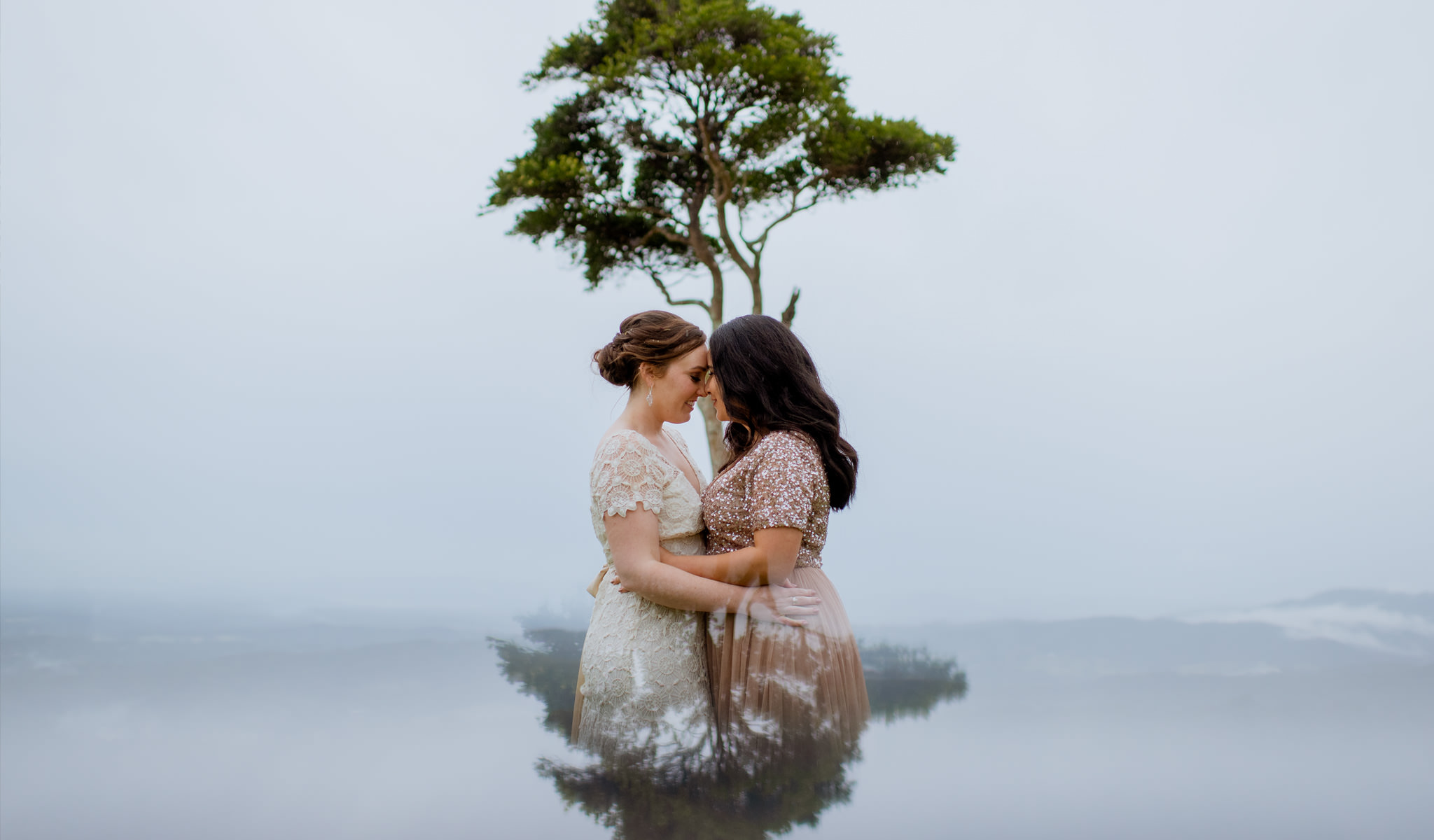 A lesbian couple putting their heads together in front of a single tree and a foggy sky