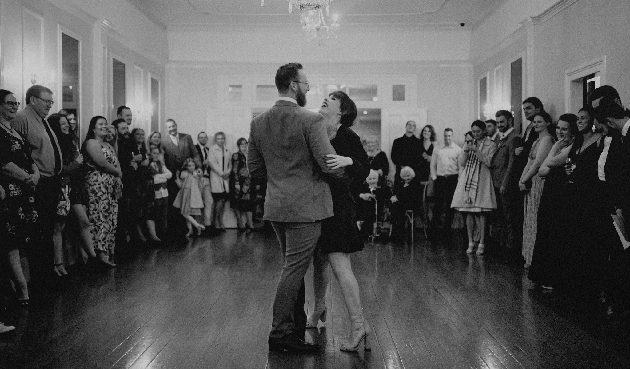 Newlyweds perform their first dance together in front of a crowd of family